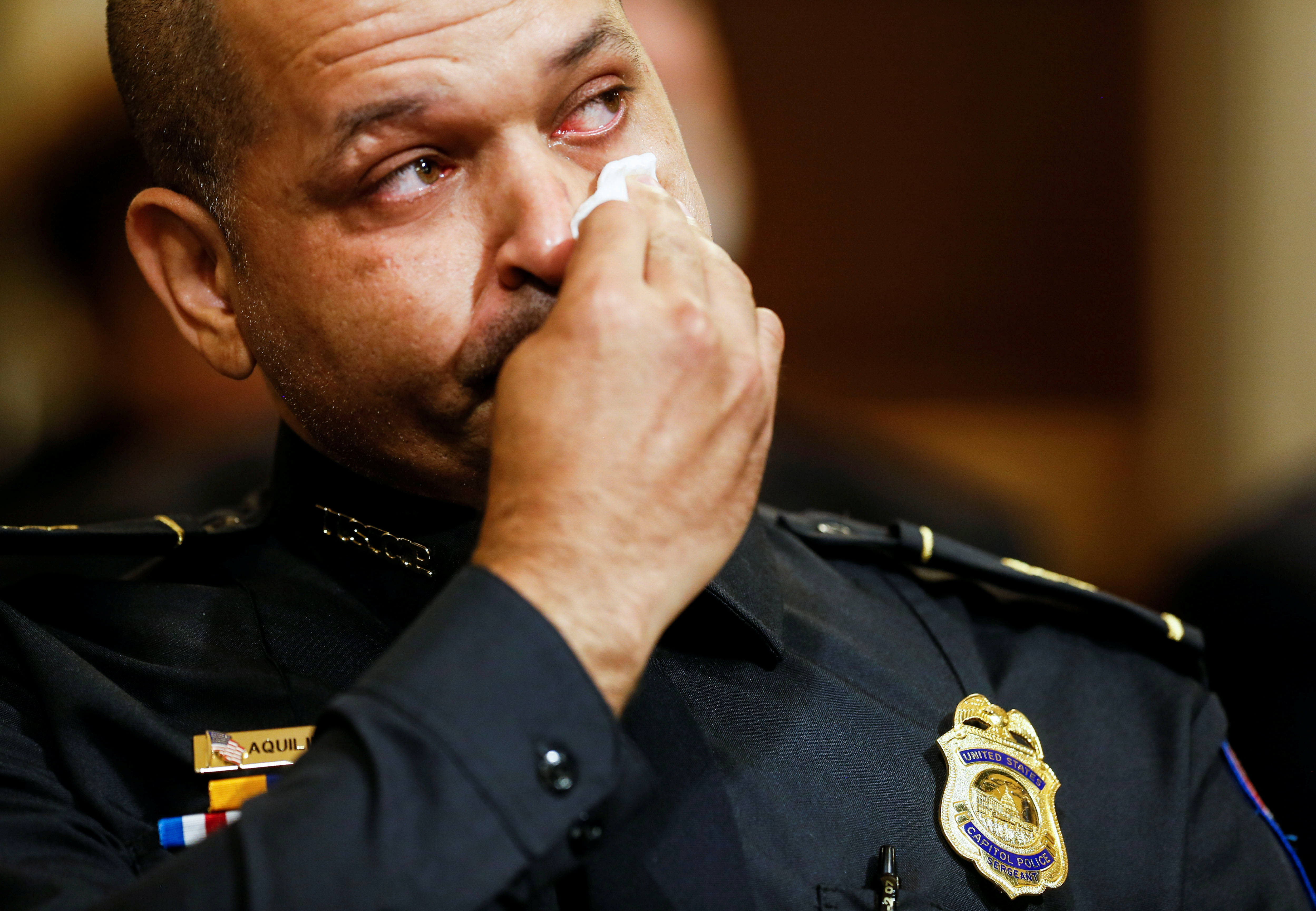 U.S. Capitol Police sergeant Aquilino Gonell wipes tears prior to testifying before the opening hearing of the U.S. House (Select) Committee investigating the January 6 attack on the U.S. Capitol, on Capitol Hill in Washington, U.S., July 27, 2021. REUTERS/Jim Bourg/Pool
