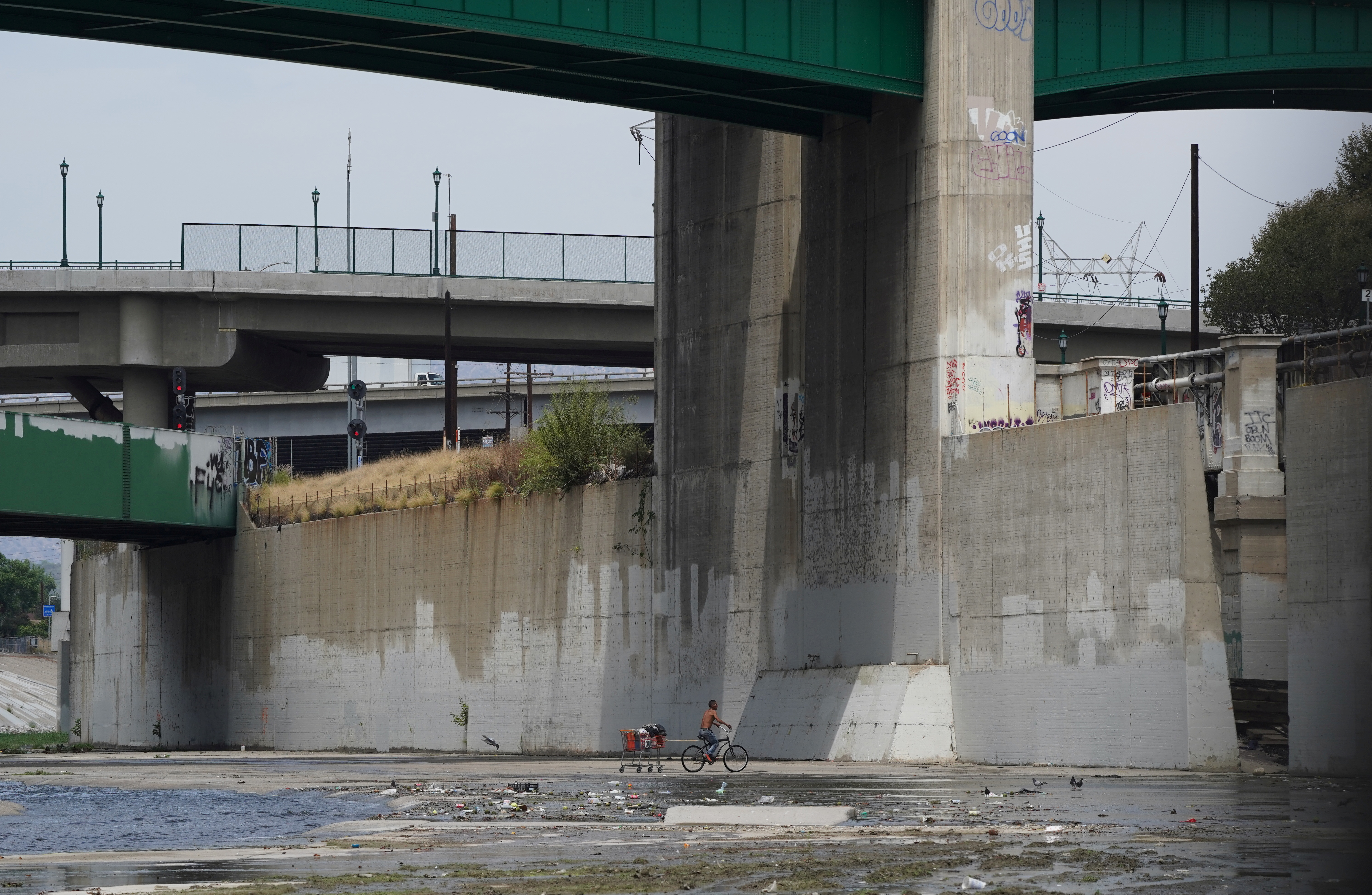 A man experiencing homelessness pulls a shopping cart on his bicycle in the Los Angeles River in Los Angeles, California, U.S. August 11, 2021. REUTERS/Bing Guan
