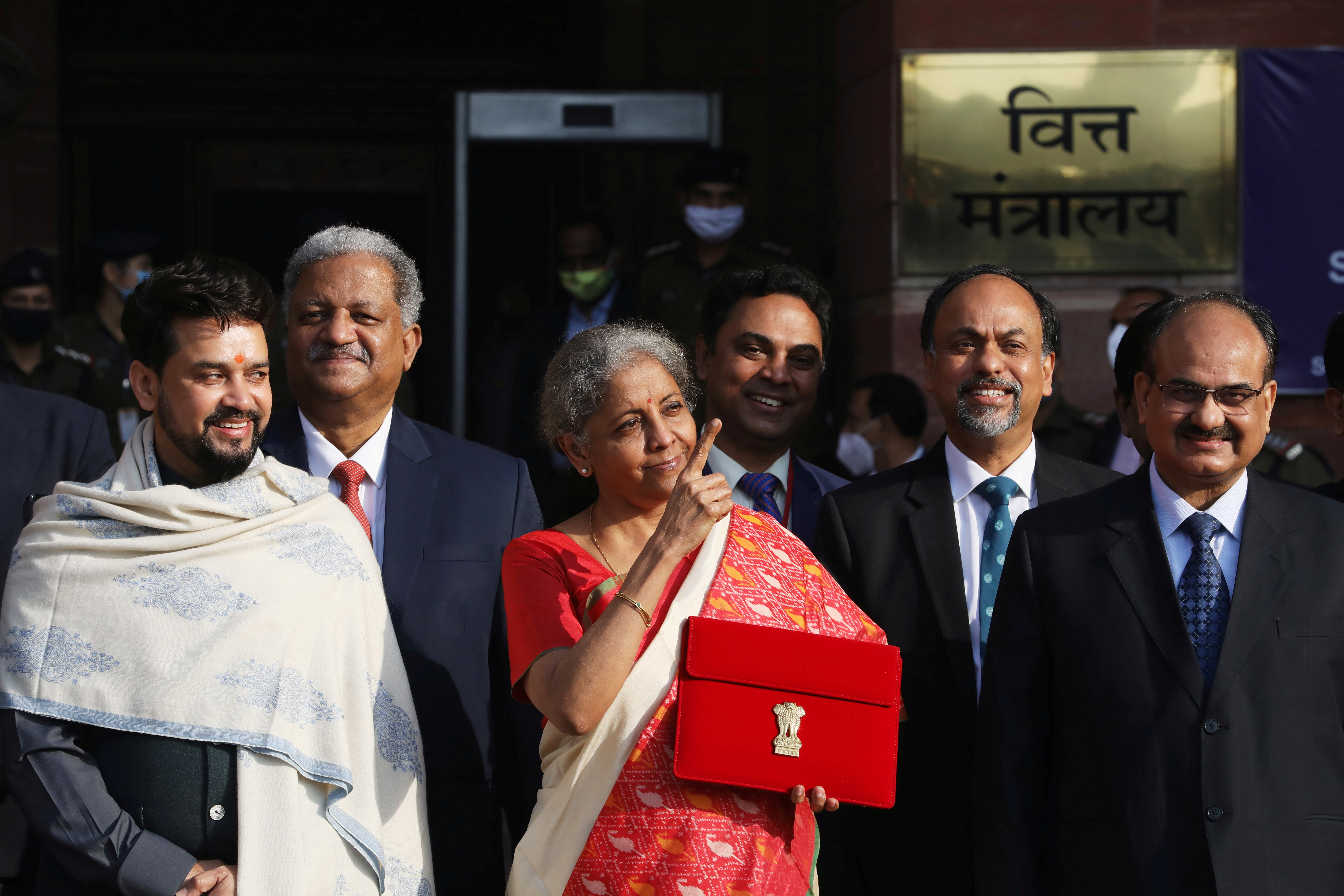 India's Finance Minister Nirmala Sitharaman stands next to Minister of State for Finance and Corporate Affairs Anurag Thakur (L) as she leaves her office to present the federal budget in the parliament in New Delhi, India, February 1, 2021. REUTERS/Anushree Fadnavis