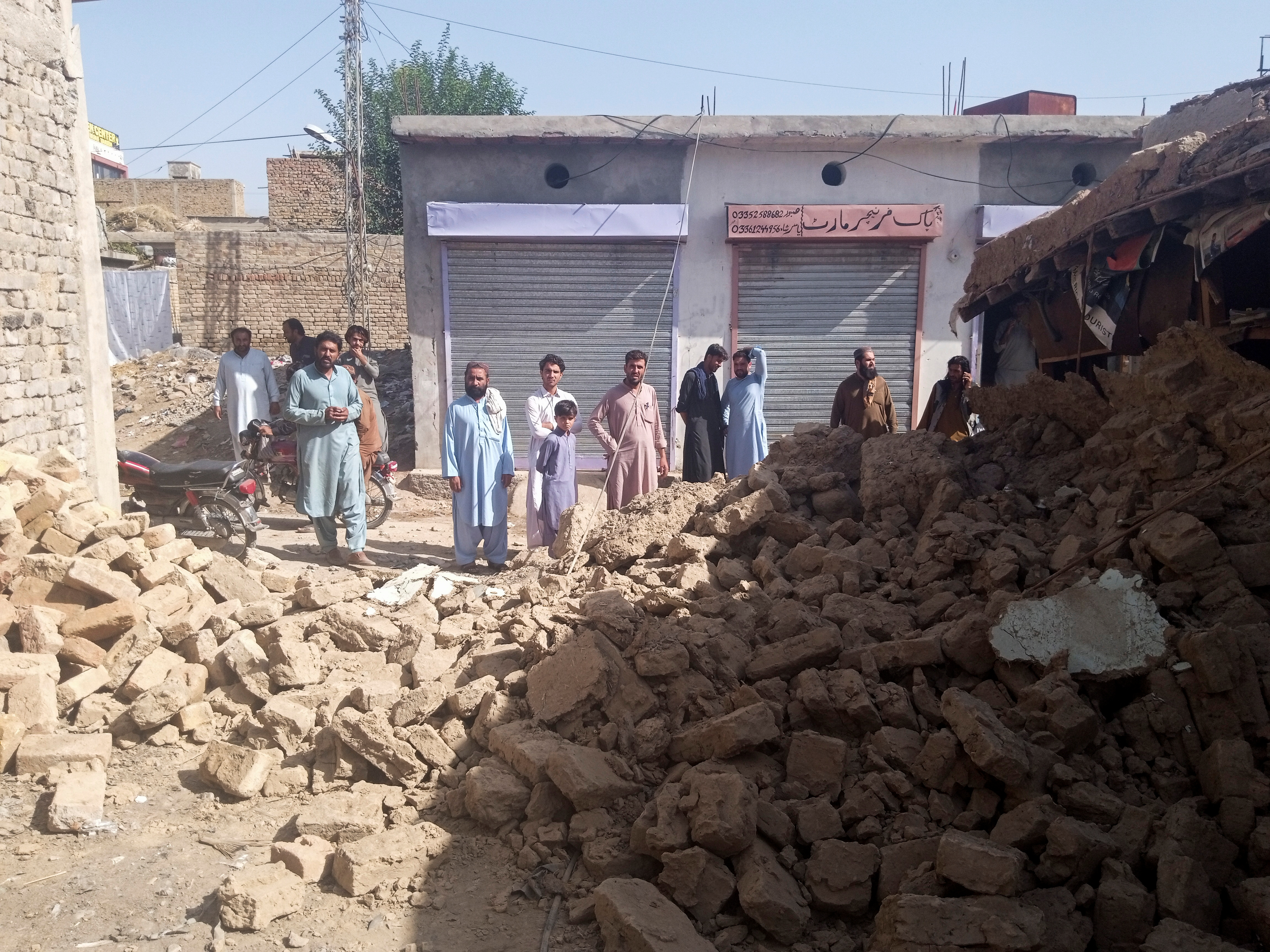 Residents gather near the rubble of a damaged house following an earthquake in Harnai, Balochistan, Pakistan, October 7, 2021. REUTERS/Naseer Ahmed