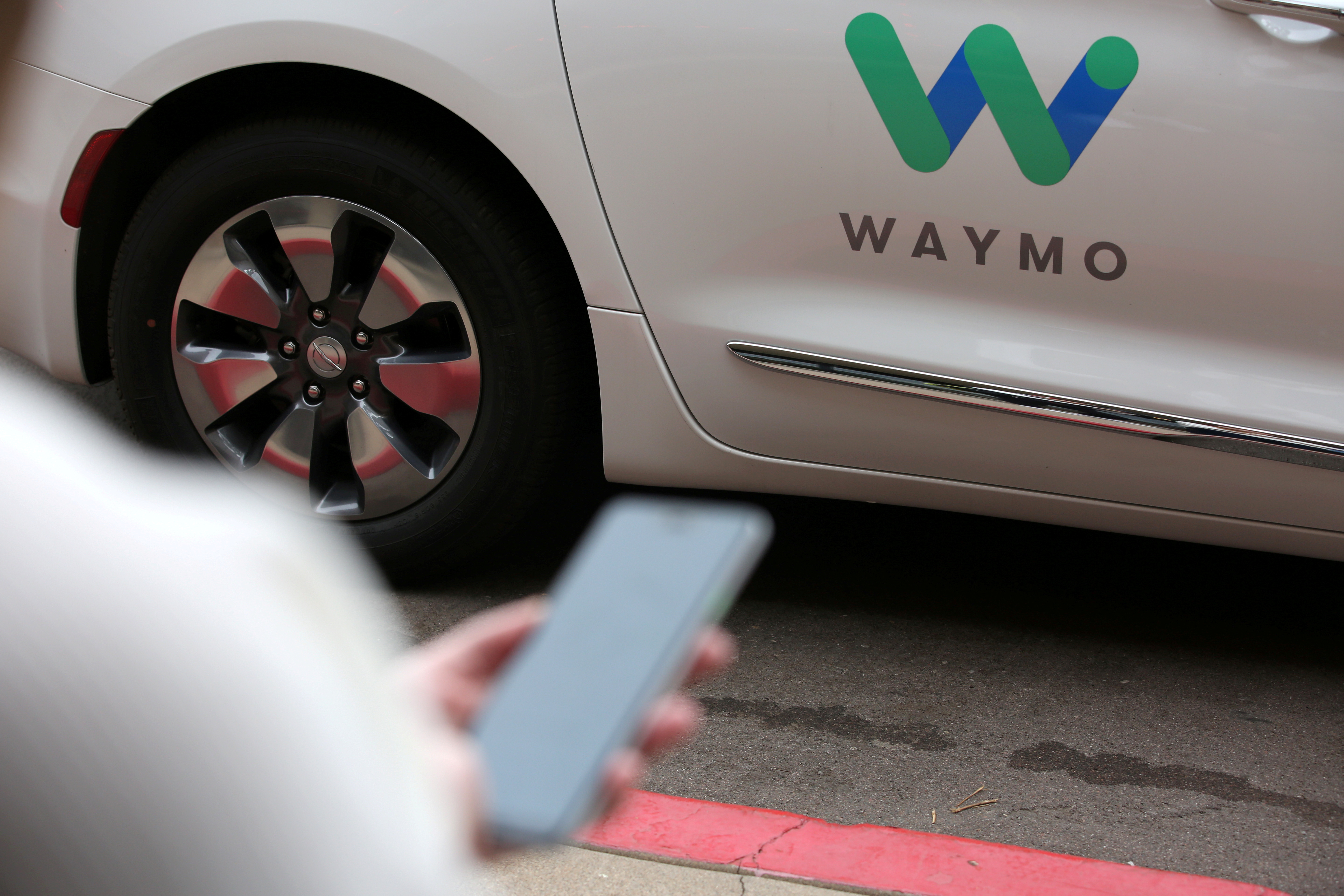 A Waymo employee hails a ride on their phone during a demonstration in Chandler, Arizona, November 29, 2018.  REUTERS/Caitlin O'Hara/File Photo