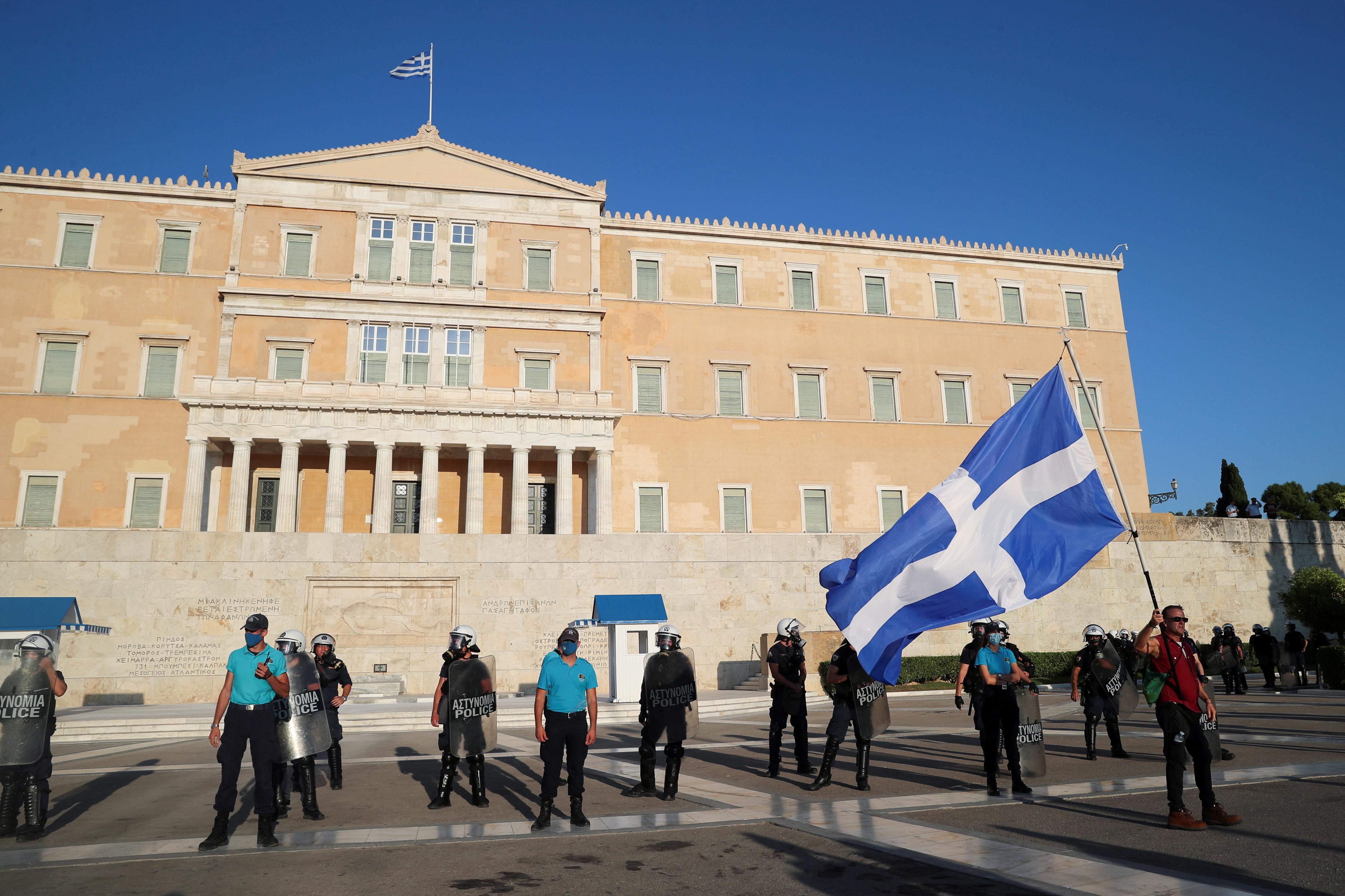 Un home té una bandera grega durant una protesta contra les vacunes contra la malaltia del coronavirus (COVID-19) fora de l'edifici del parlament, a Atenes, Grècia, el 29 d'agost de 2021. REUTERS / Costas Baltas