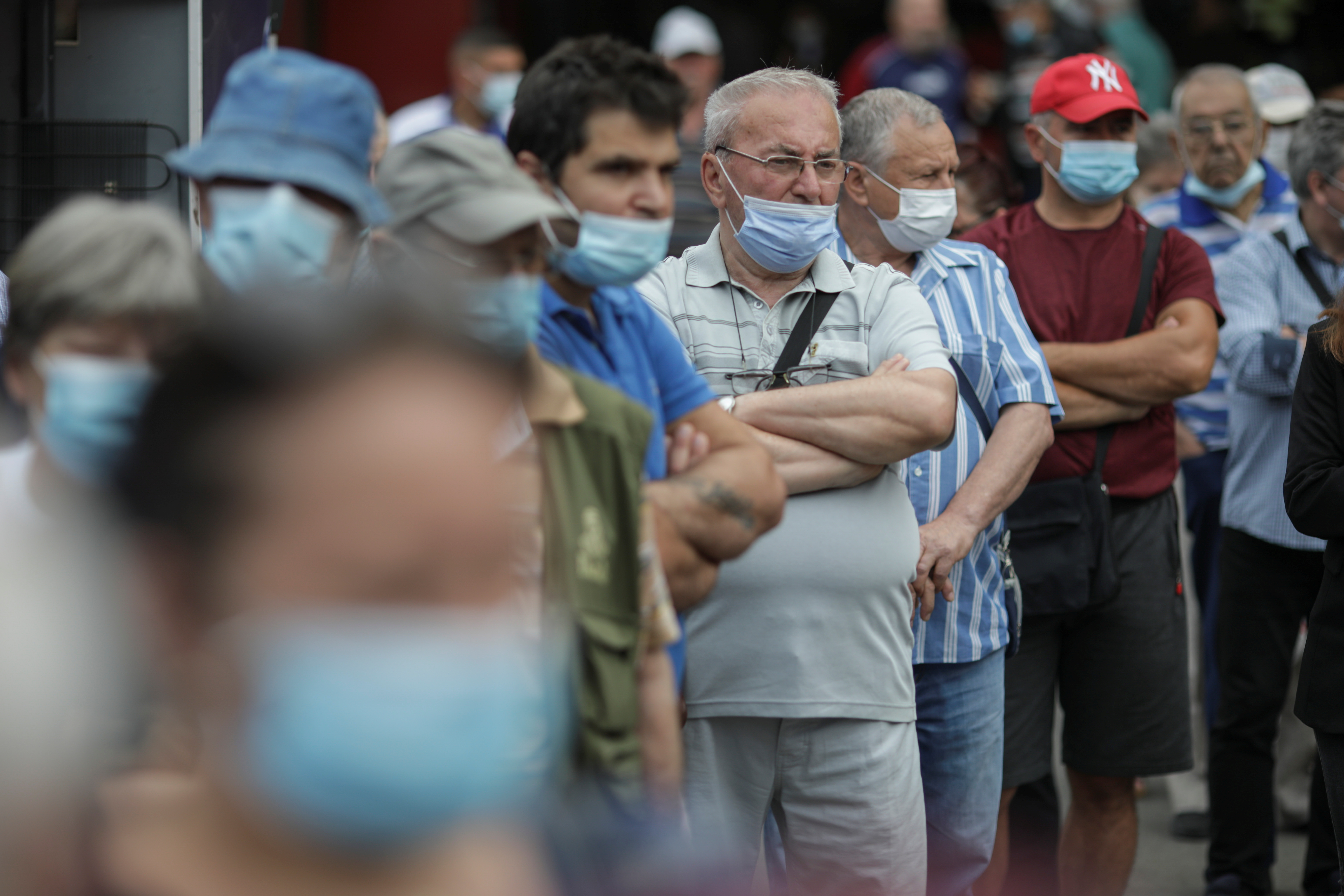 People wait in line to receive a COVID-19 vaccine at a mobile vaccination center in Bucharest, Romania, June 11, 2021. Inquam Photos/Octav Ganea via REUTERS