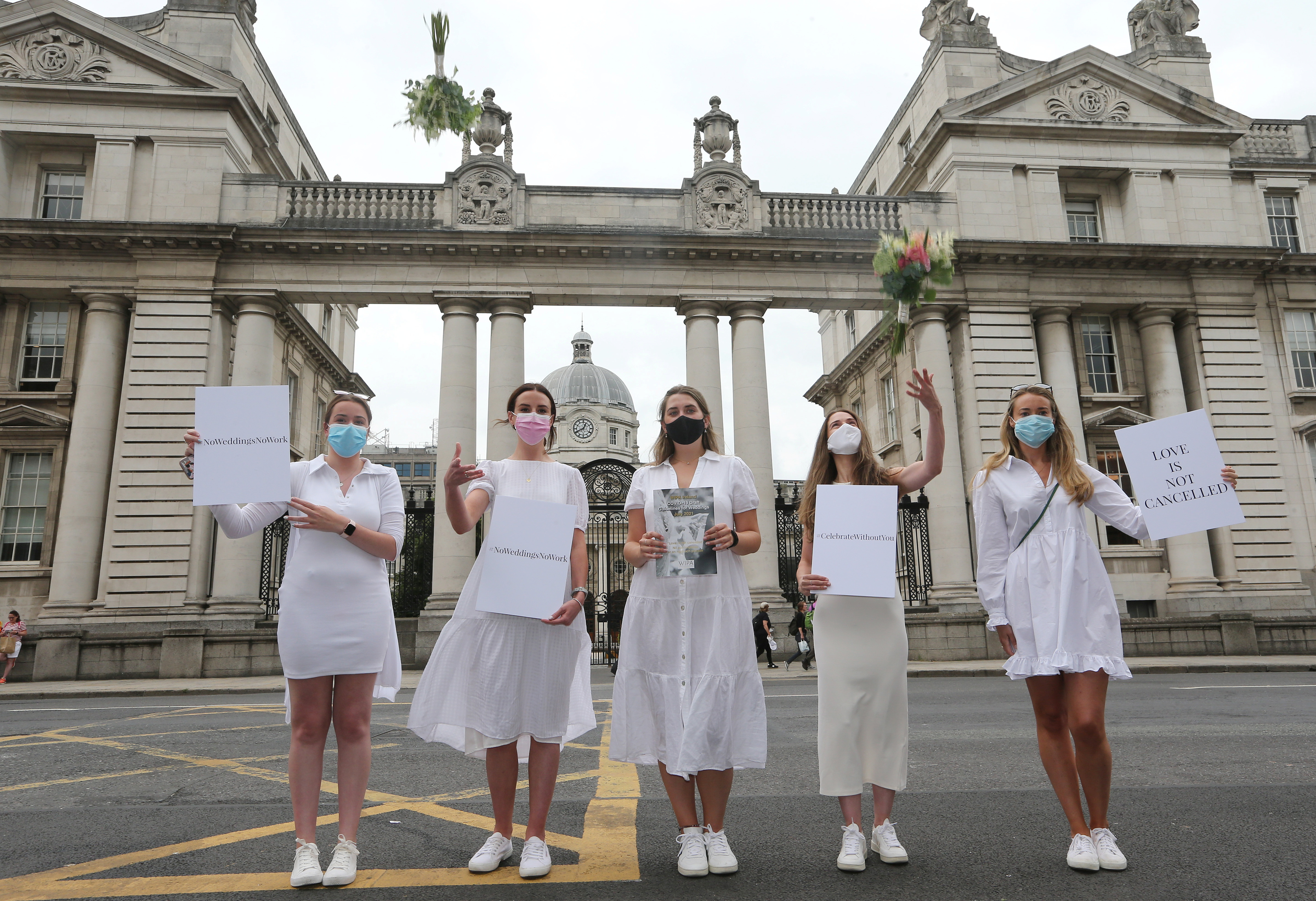 Orla Hogan, Ali O'Mara, Brana Culle, Anna Killeen and Orla O'Huadaigh hold up signs at a protest march to Government Buildings in a bid to allow up to 100 guests to attend weddings this year in Dublin, Ireland, July 27, 2021. REUTERS/Lorraine O'Sullivan