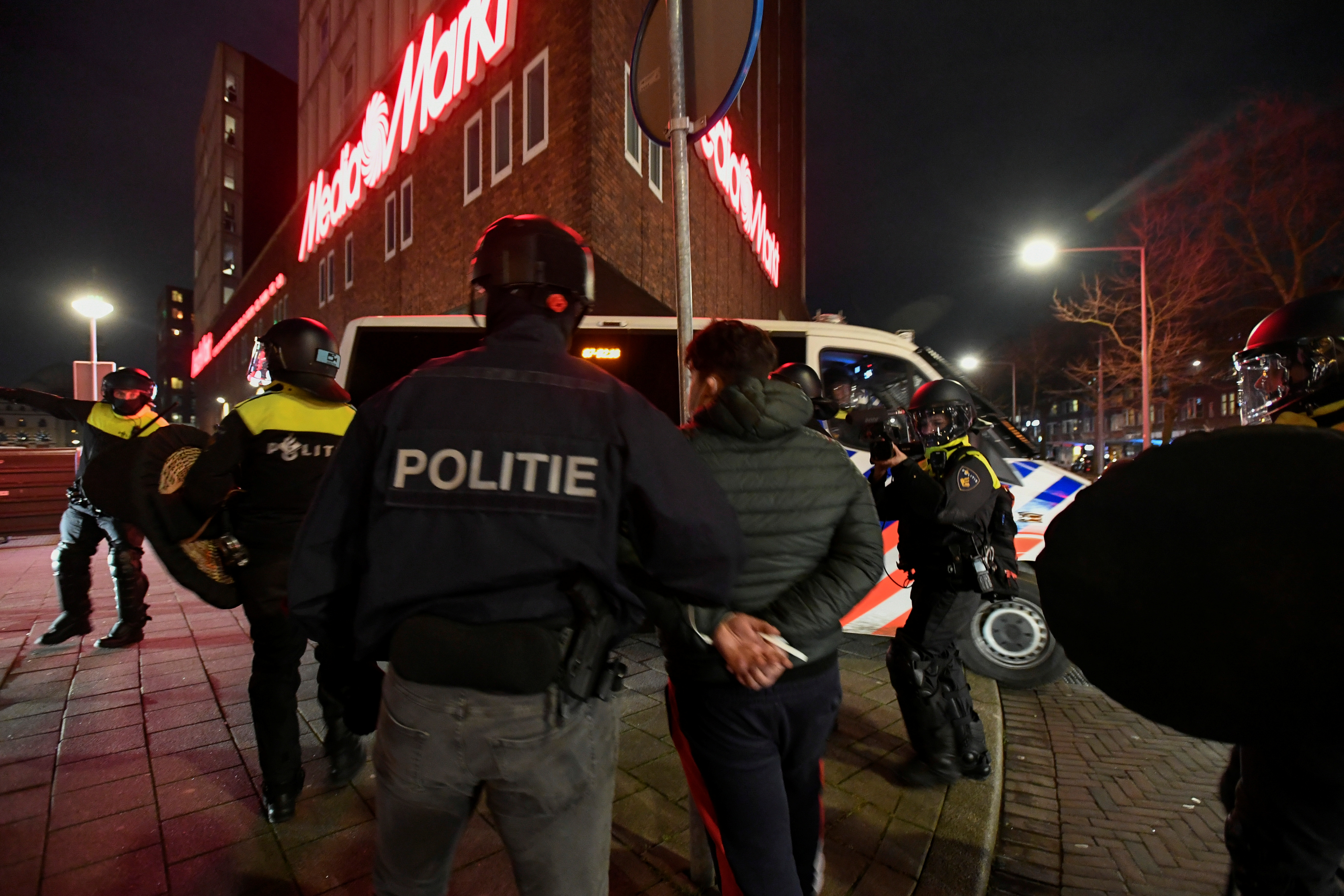 Police officers detain a demonstrator protesting against restrictions put in place to curb the spread of the coronavirus disease (COVID-19) in Rotterdam, Netherlands, January 26, 2021. REUTERS/Stringer