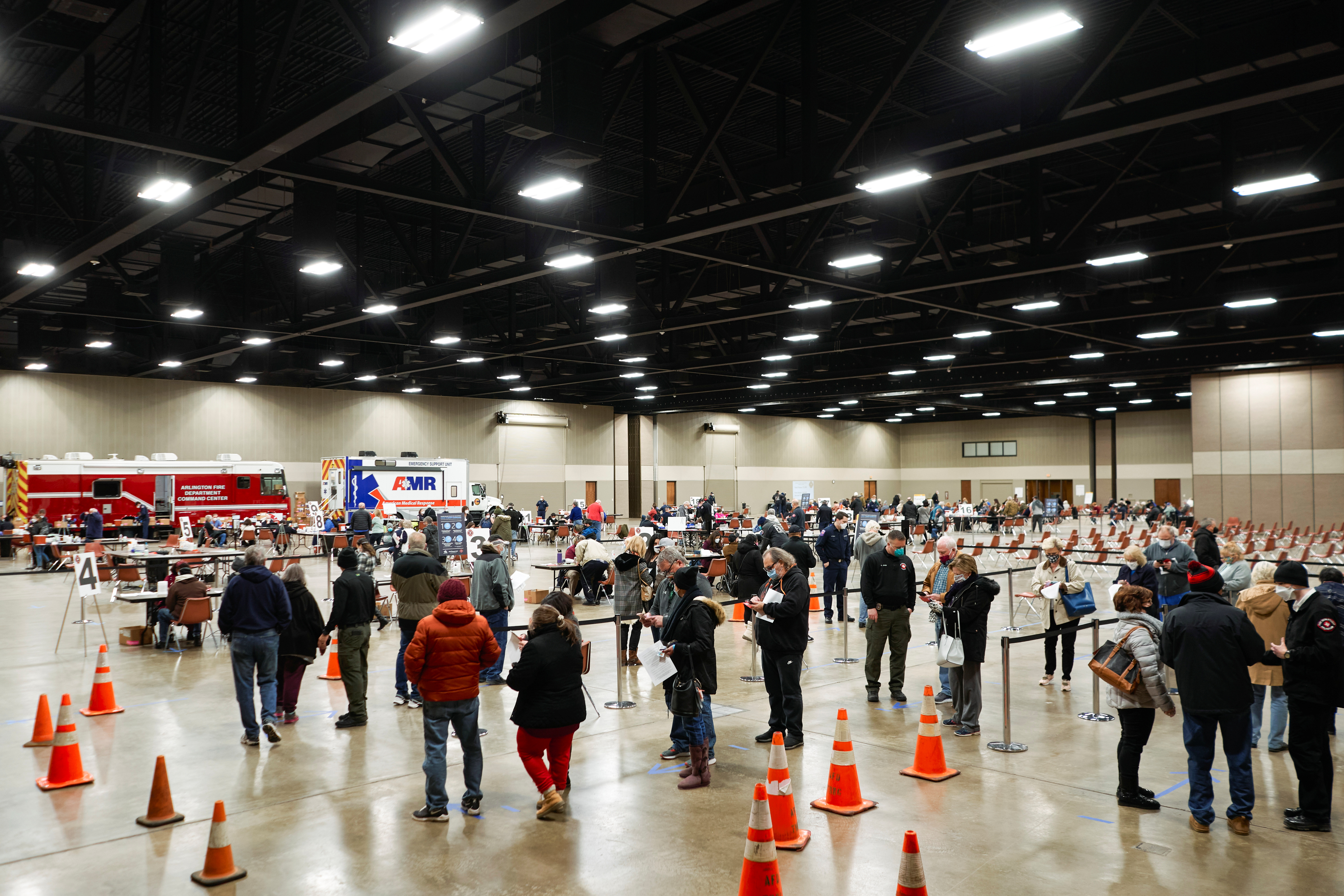 People wait in line to be inoculated against the coronavirus disease (COVID-19) at a vaccination site at the Esports Stadium Arlington & Expo Center in Arlington, Texas, U.S. February 12, 2021.  REUTERS/Cooper Neill