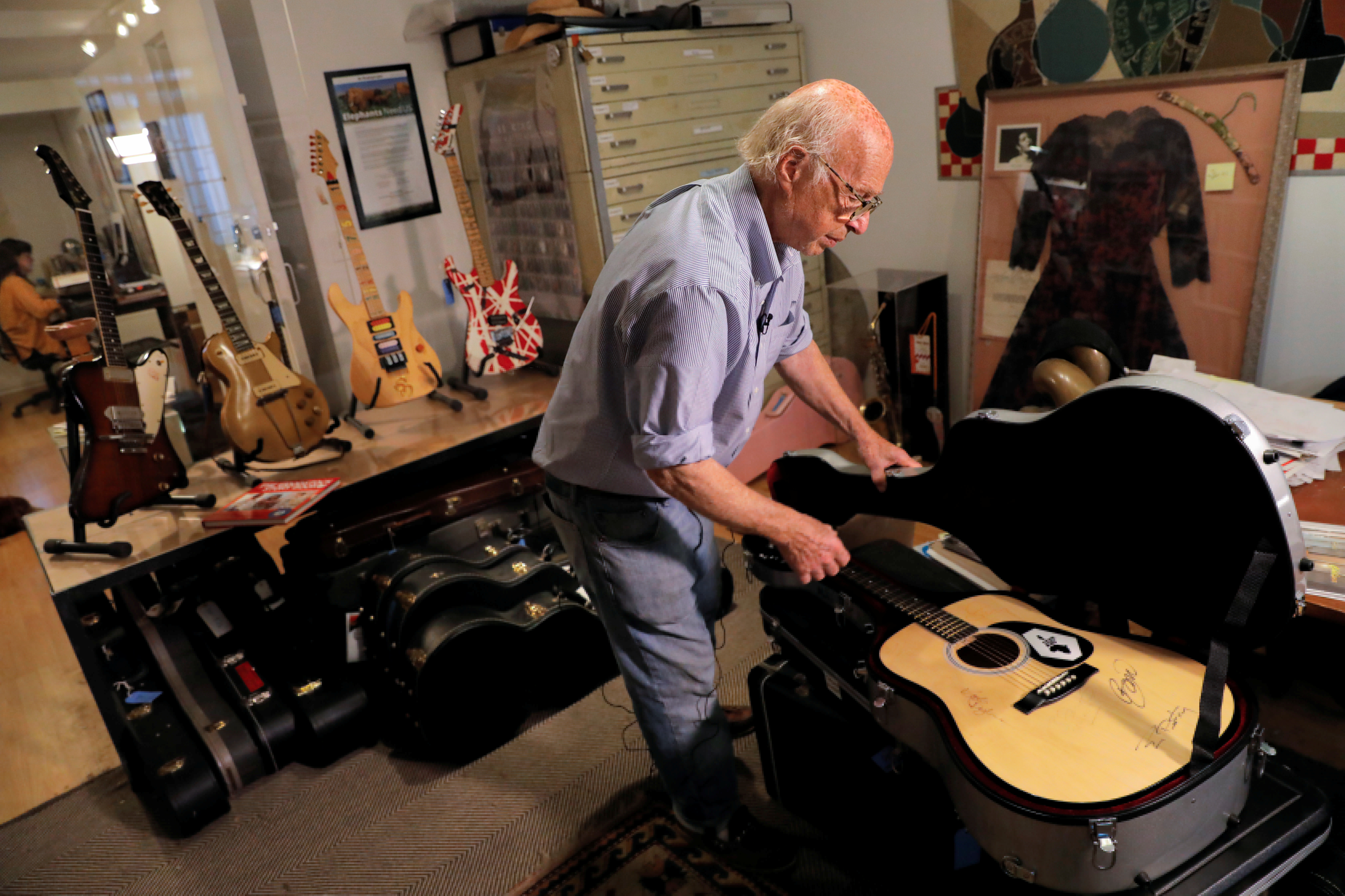 Arlan Ettinger, president and founder of Guernsey's auction house, displays a Live Aid guitar signed by Bob Geldof, Tom Petty, Bob Dylan, Bono and Sting among others ahead of their