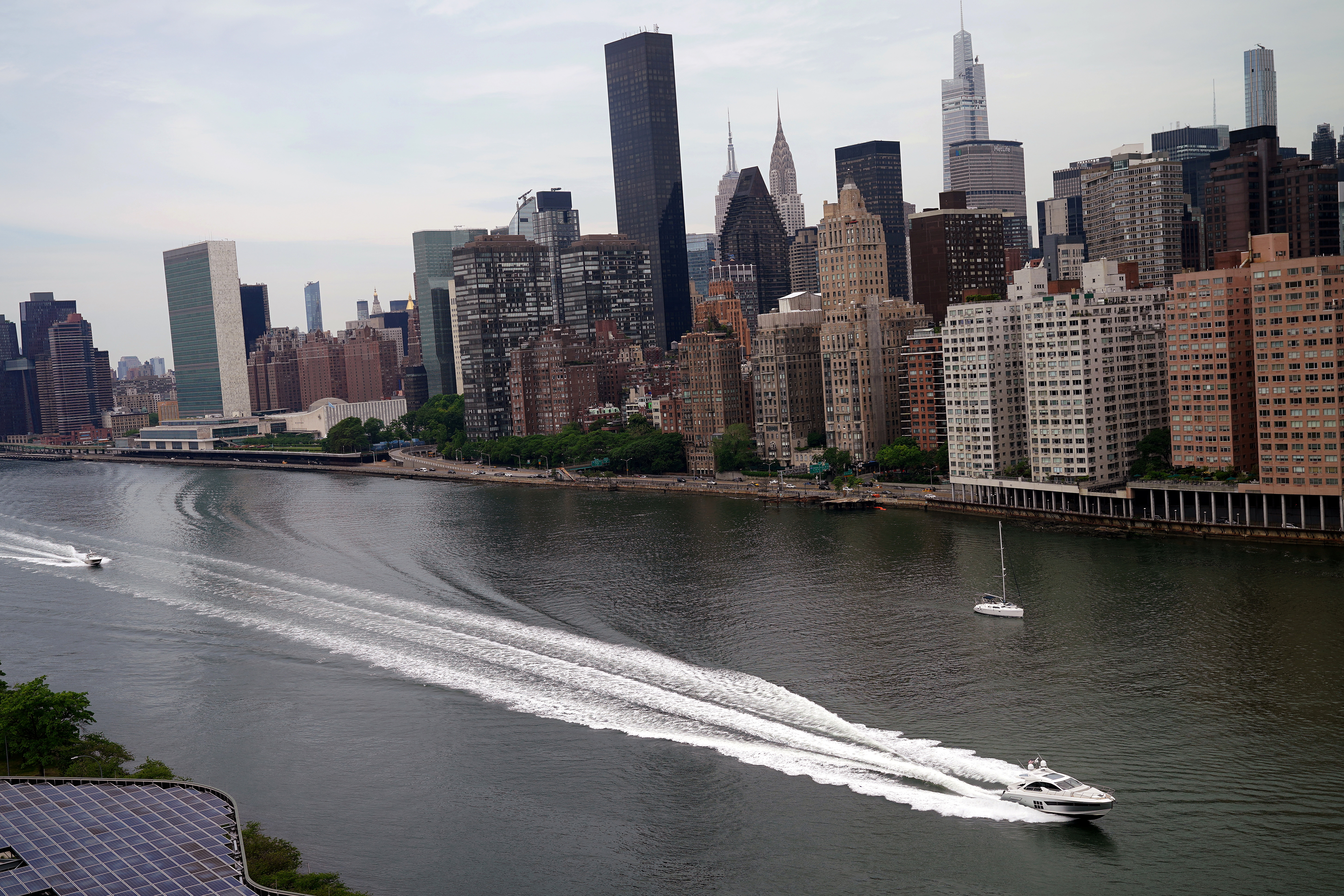 A boat passes by Manhattan as pictured from the Graduate Roosevelt Island hotel in New York City, New York, U.S., June 2, 2021.  REUTERS/Carlo Allegri