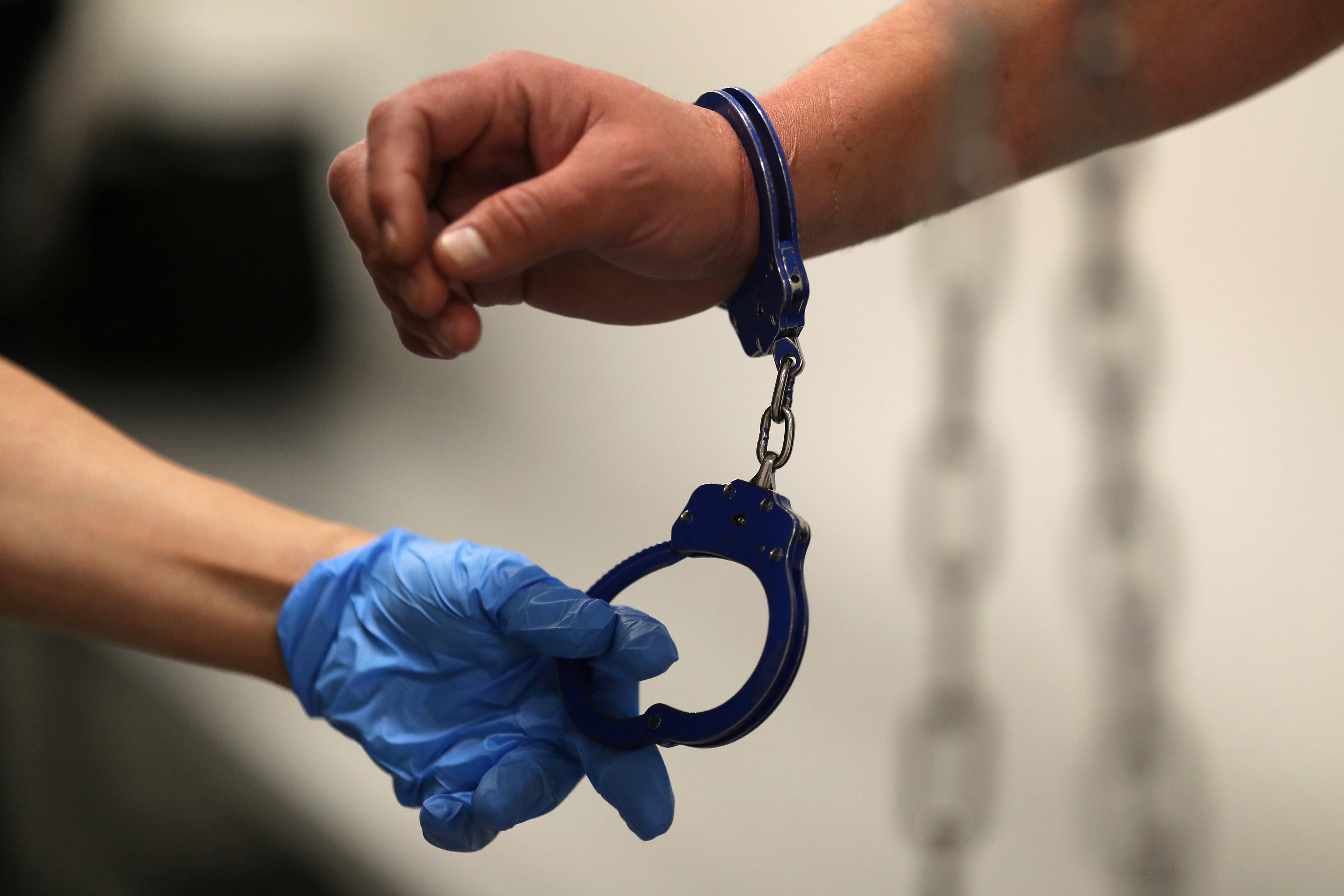 An Immigration and Customs Enforcement's (ICE) Fugitive Operations Agent takes handcuffs off before booking an immigrant in Los Angeles, California, U.S., March 1, 2020. REUTERS/Lucy Nicholson