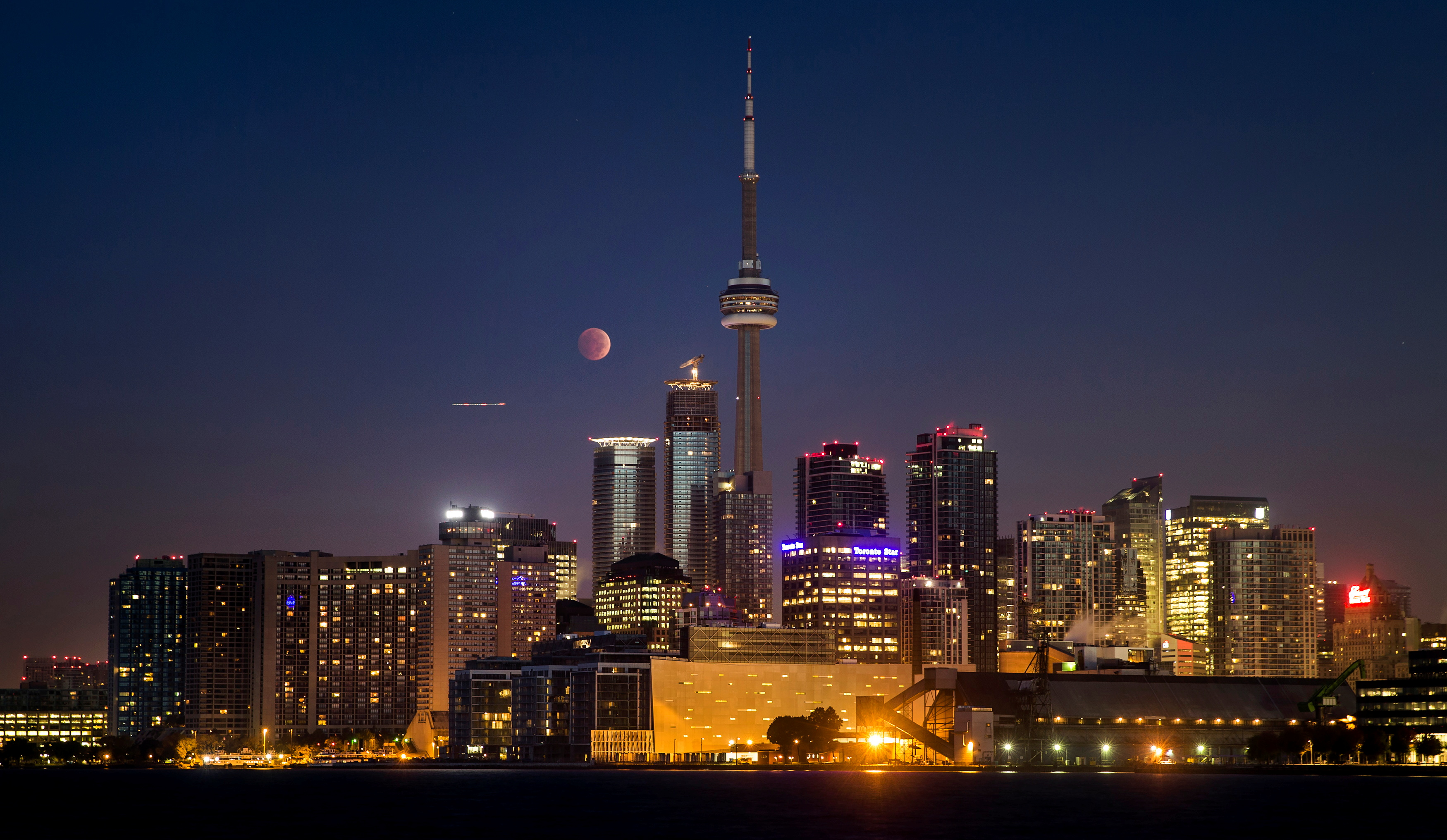 The moon turns orange during a total lunar eclipse behind the CN Tower and the skyline during moonset in Toronto, October 8, 2014. REUTERS/Mark Blinch/File Photo