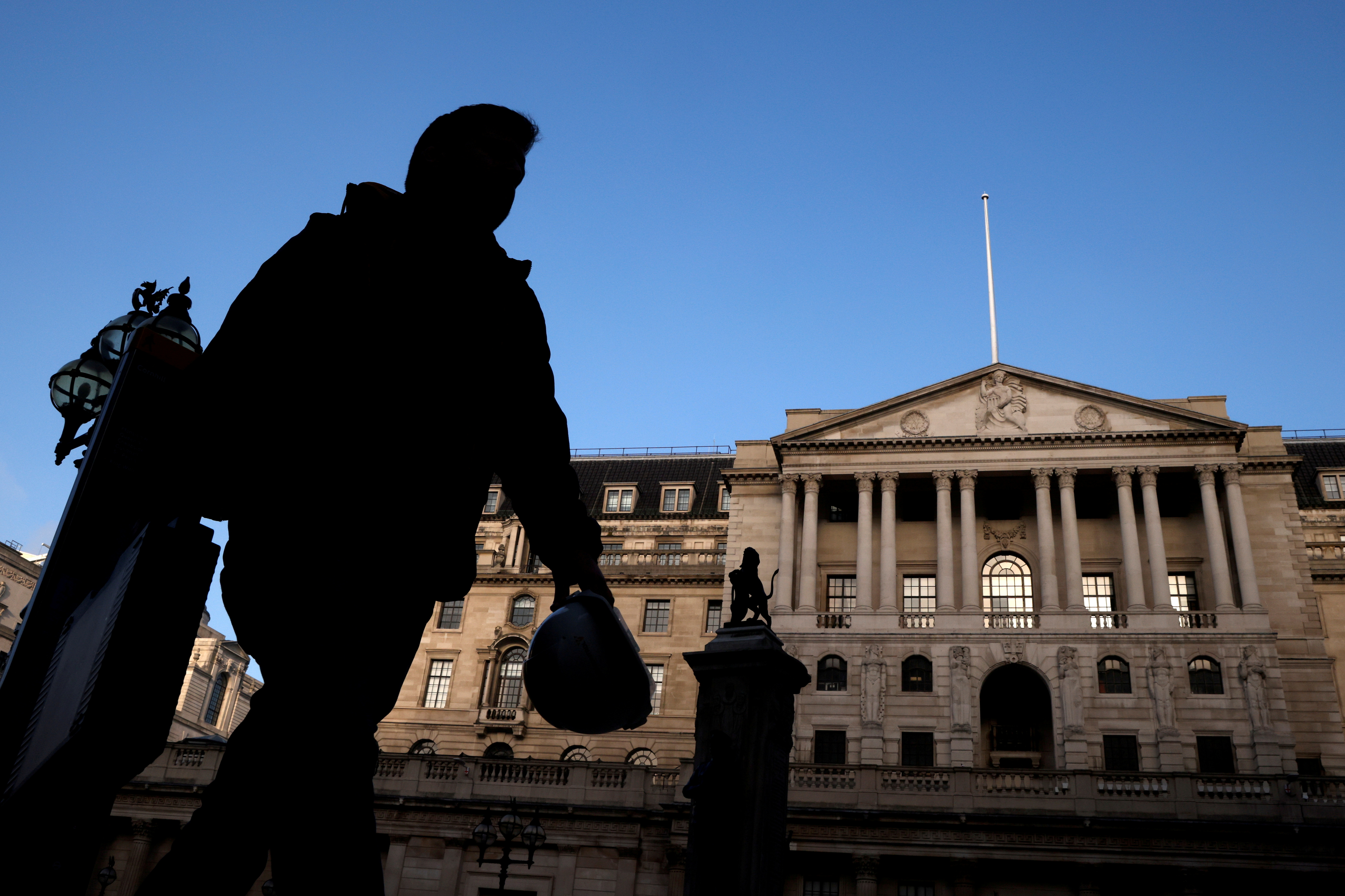 A person is silhouetted as he walks past The Bank of England, amid the outbreak of the coronavirus disease (COVID-19), in London, Britain, November 5, 2020. REUTERS/John Sibley