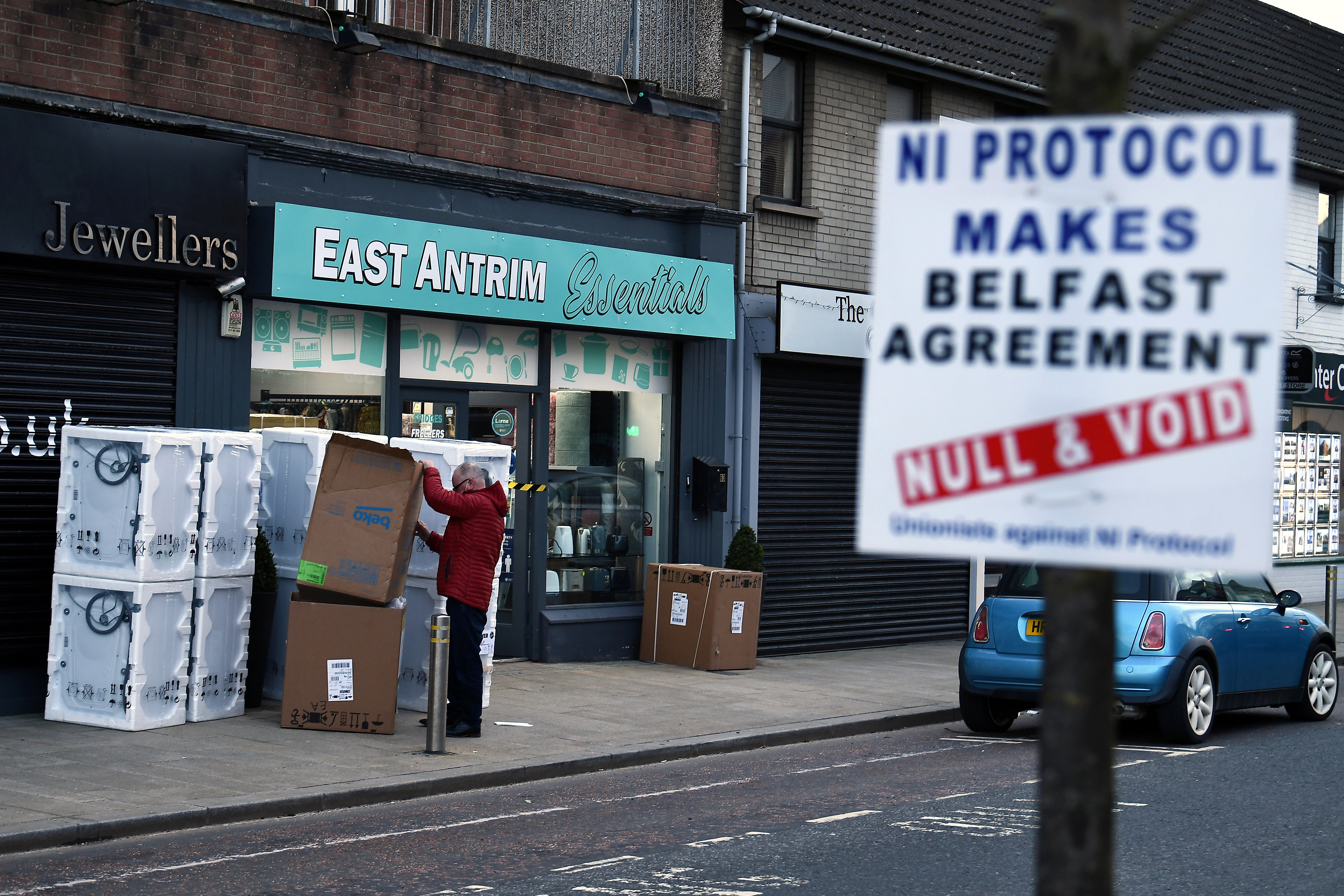 A man sorts through a delivery of washing machines with a sign is seen across the road featuring a message against the Brexit border checks in relation to the Northern Ireland protocol in the town centre of Larne, Northern Ireland. February 12, 2021. REUTERS/Clodagh Kilcoyne/File Photo