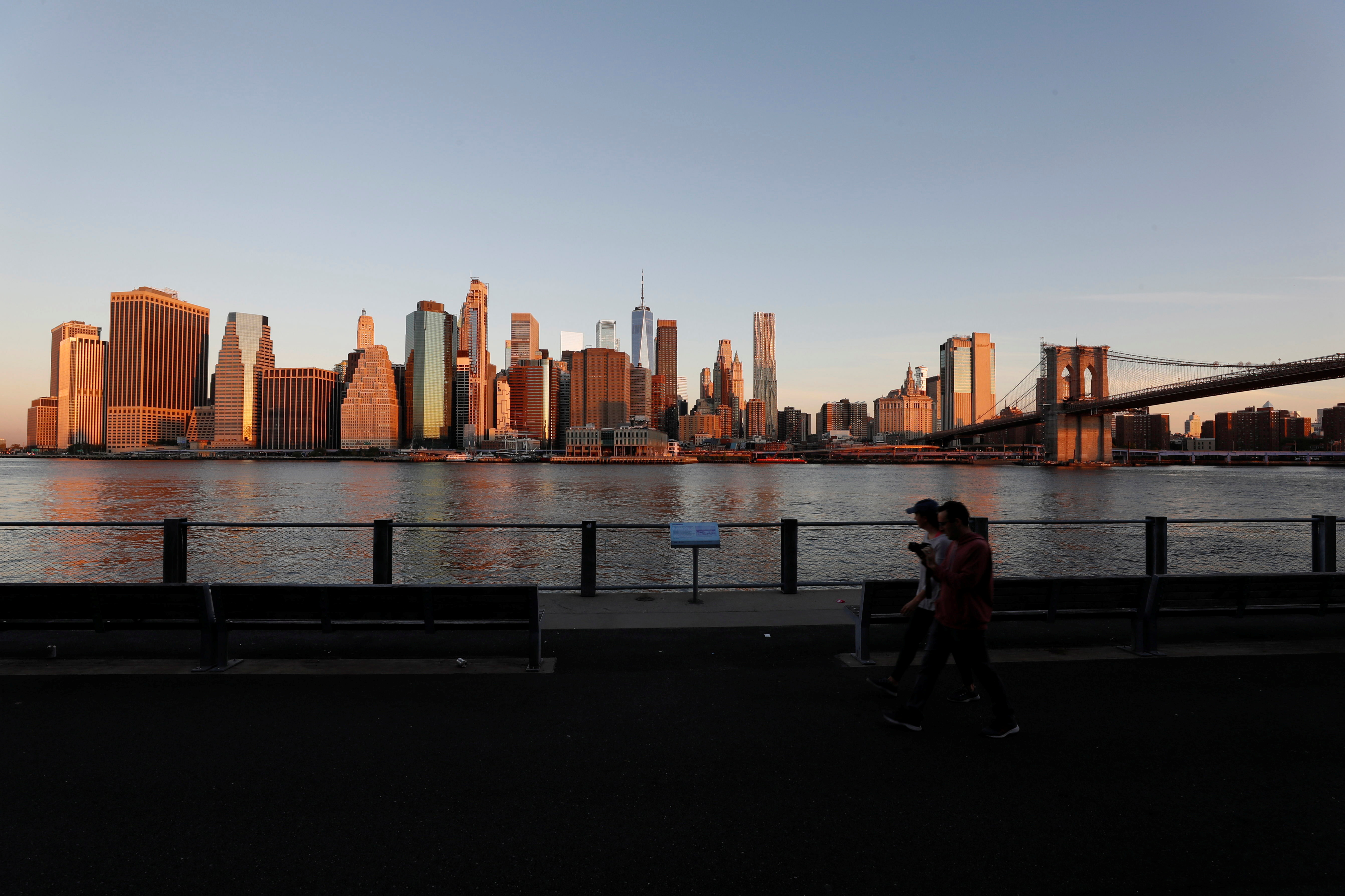 People walk as the New York skyline and the Brooklyn Bridge are seen on the 20th anniversary of the September 11, 2001 attacks in New York City, New York, U.S., September 11, 2021. REUTERS/Mario Anzuoni