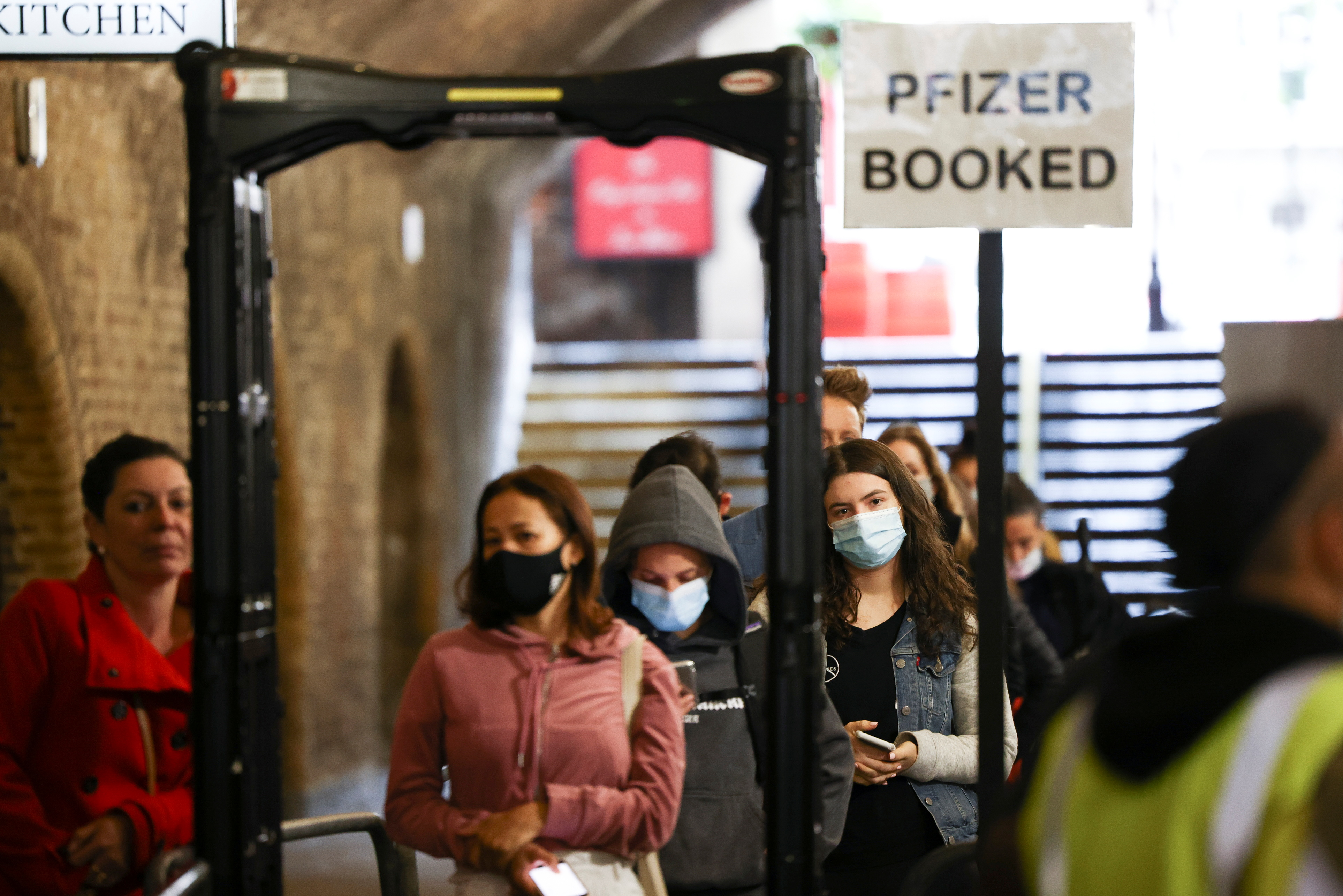People queue to receive a dose of the Pfizer BioNTech vaccine at an NHS vaccination centre hosted at the Heaven nightclub, amid the coronavirus disease (COVID-19) pandemic, in London, Britain, August 8, 2021. REUTERS/Henry Nicholls