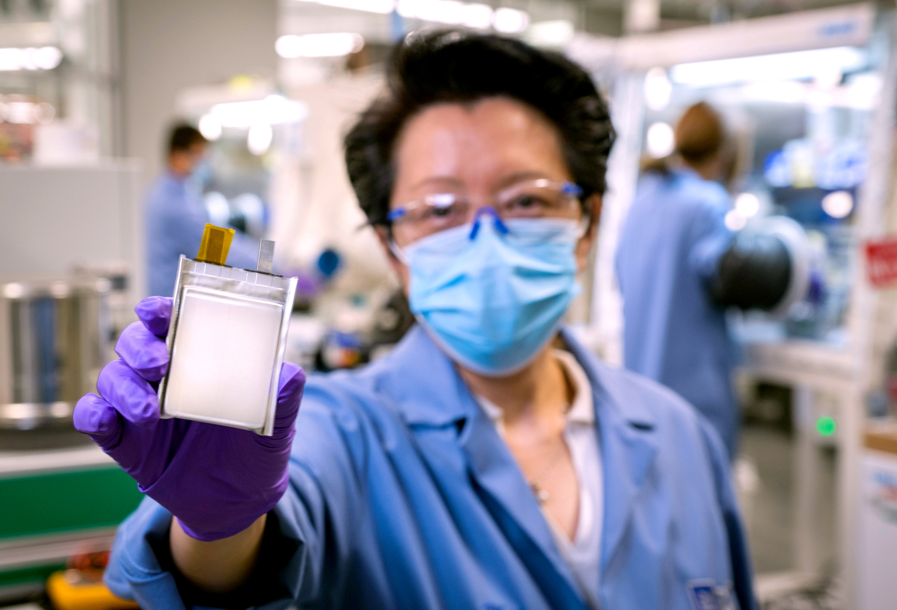 A GM employee poses with an example of the company's next-generation lithium metal batteries at  GM Chemical and Materials Systems Lab in Warren, Michigan, U.S. September 9, 2020. Picture taken September 9, 2020.   Steve Fecht/General Motors/Handout via REUTERS.