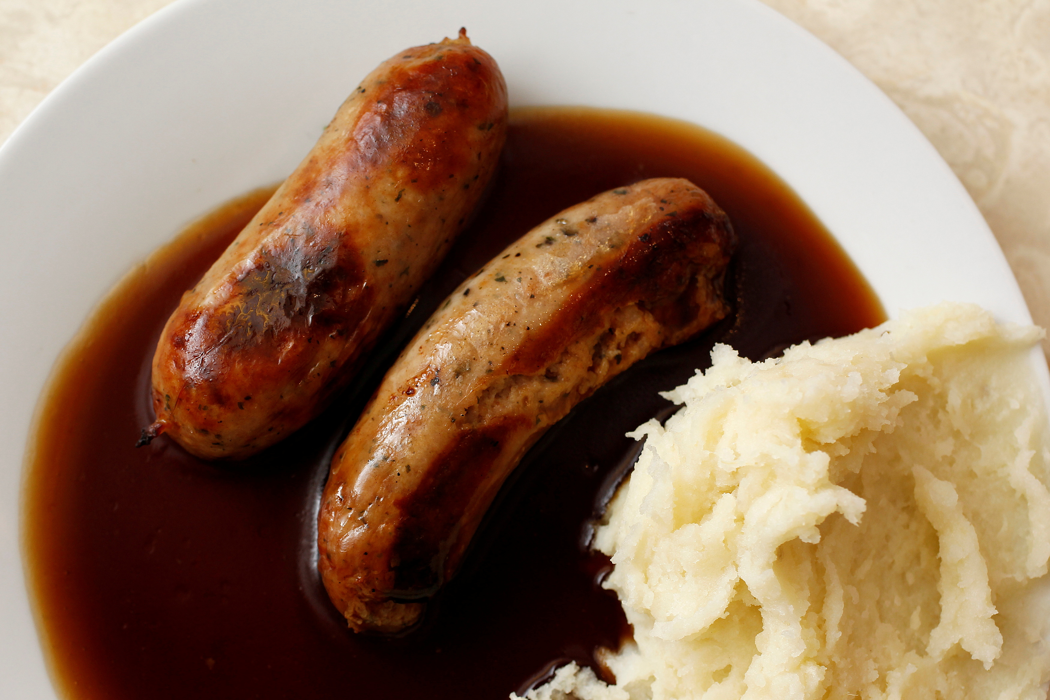 A traditional British meal of sausages and mashed potato in gravy, known as Bangers and Mash, is pictured in G. Kelly's pie and mash shop in east London June 1, 2012. REUTERS/Suzanne Plunkett/File Photo