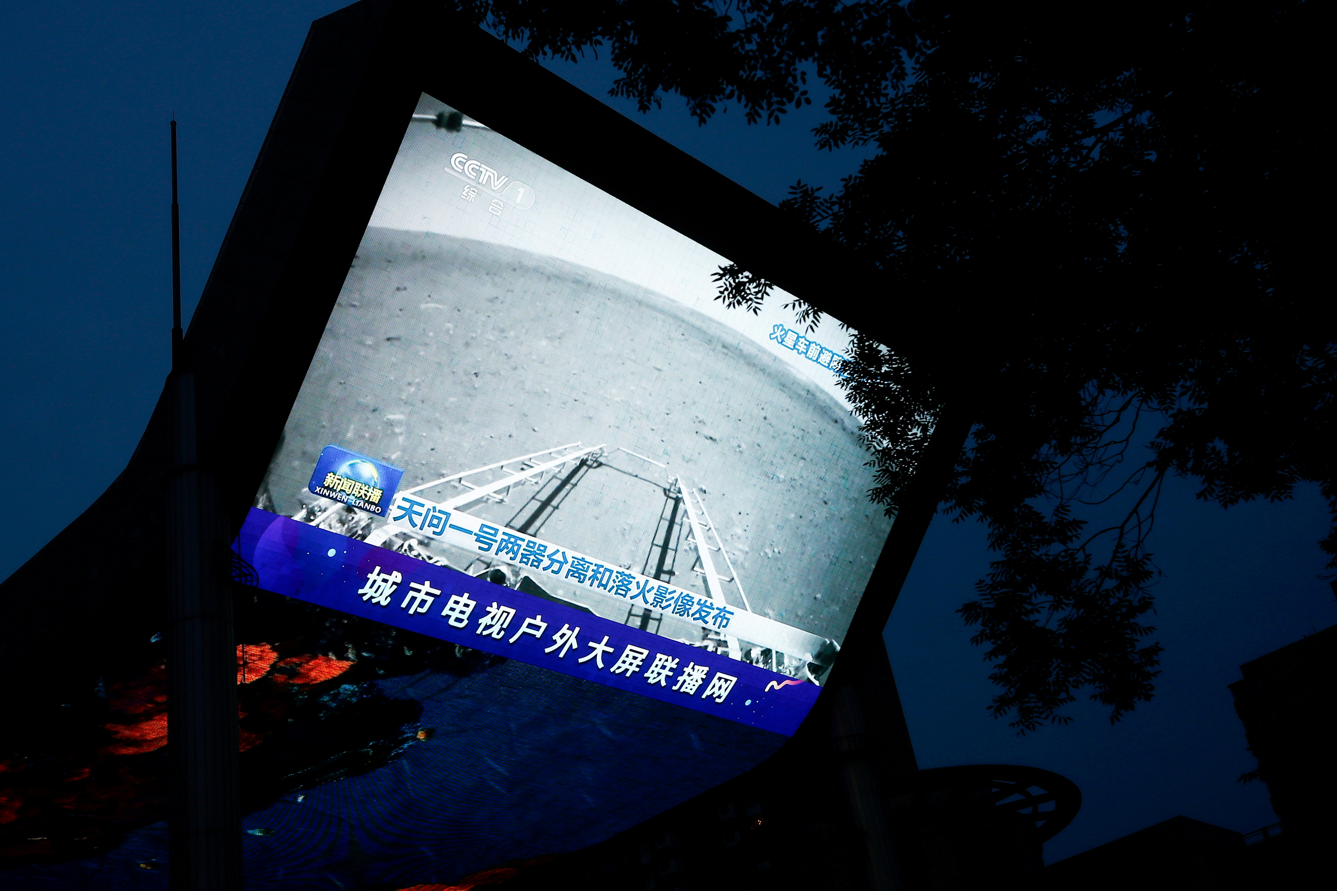 A screen broadcasts a CCTV state media news bulletin, showing an image of Mars taken by Chinese Mars rover Zhurong as part of the Tianwen-1 mission, in Beijing, China, May 19, 2021. REUTERS/Thomas Peter