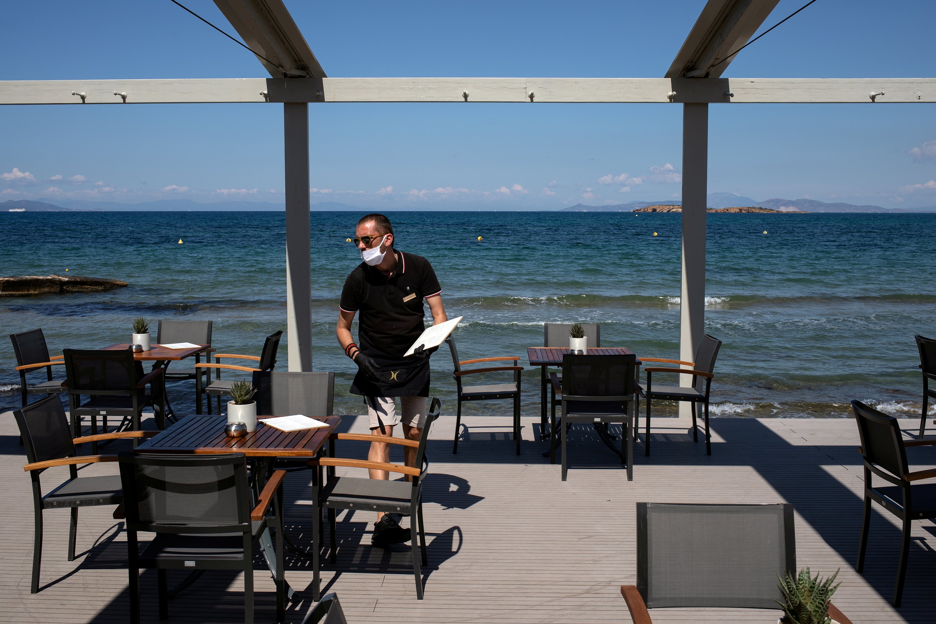 An employee wearing a protective mask, leaves a menu on a table at the beach bar of the Divani Apollon Palace hotel, on the first day of the opening of hotels in Greece, following a nationwide lockdown against the spread of the coronavirus disease (COVID-19), in Athens, Greece, June 1, 2020. REUTERS/Alkis Konstantinidis