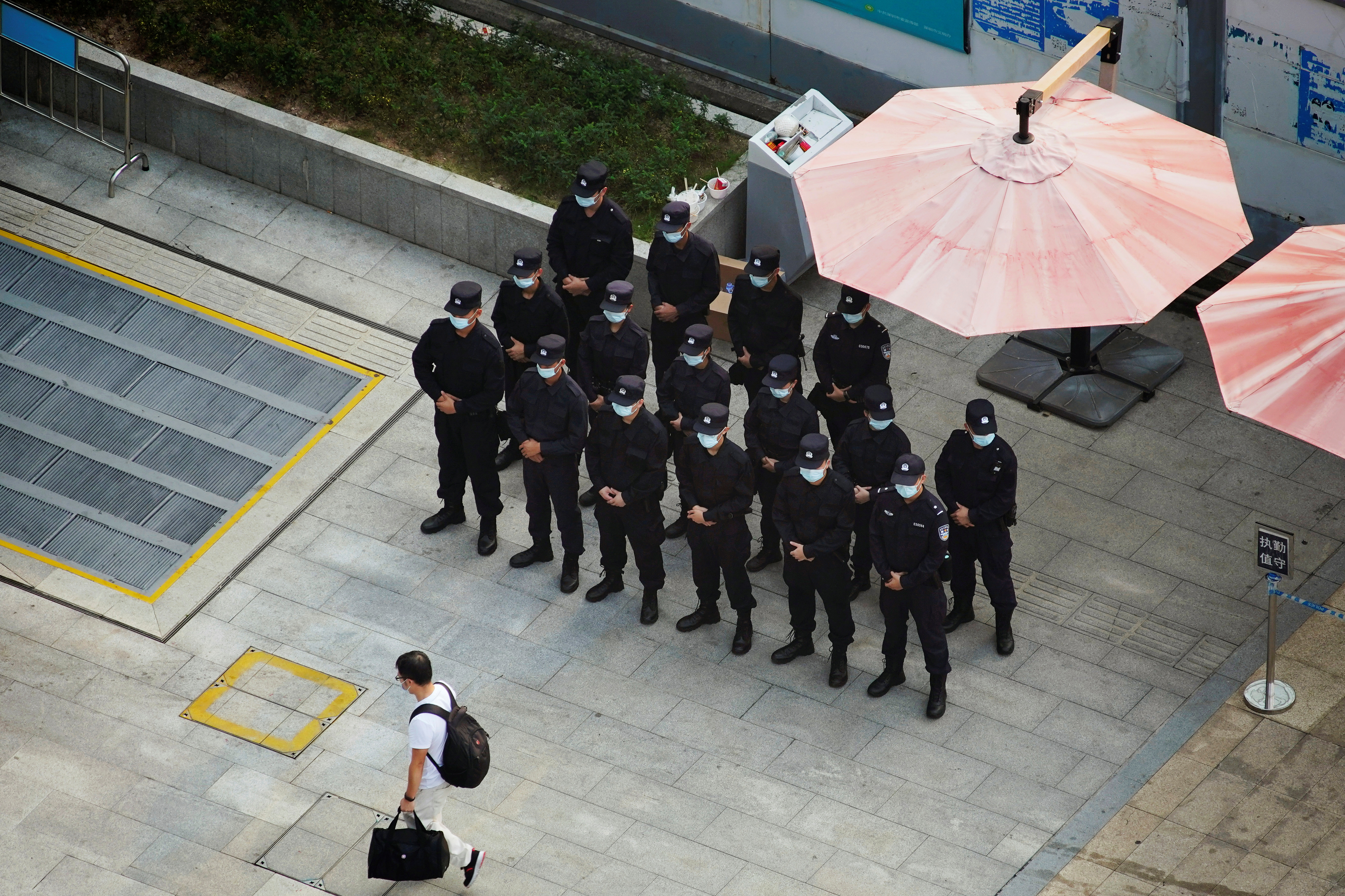 A man walks past security personnel standing on duty outside the headquarters of China Evergrande Group in Shenzhen, Guangdong province, China, September 30, 2021. REUTERS/Aly Song