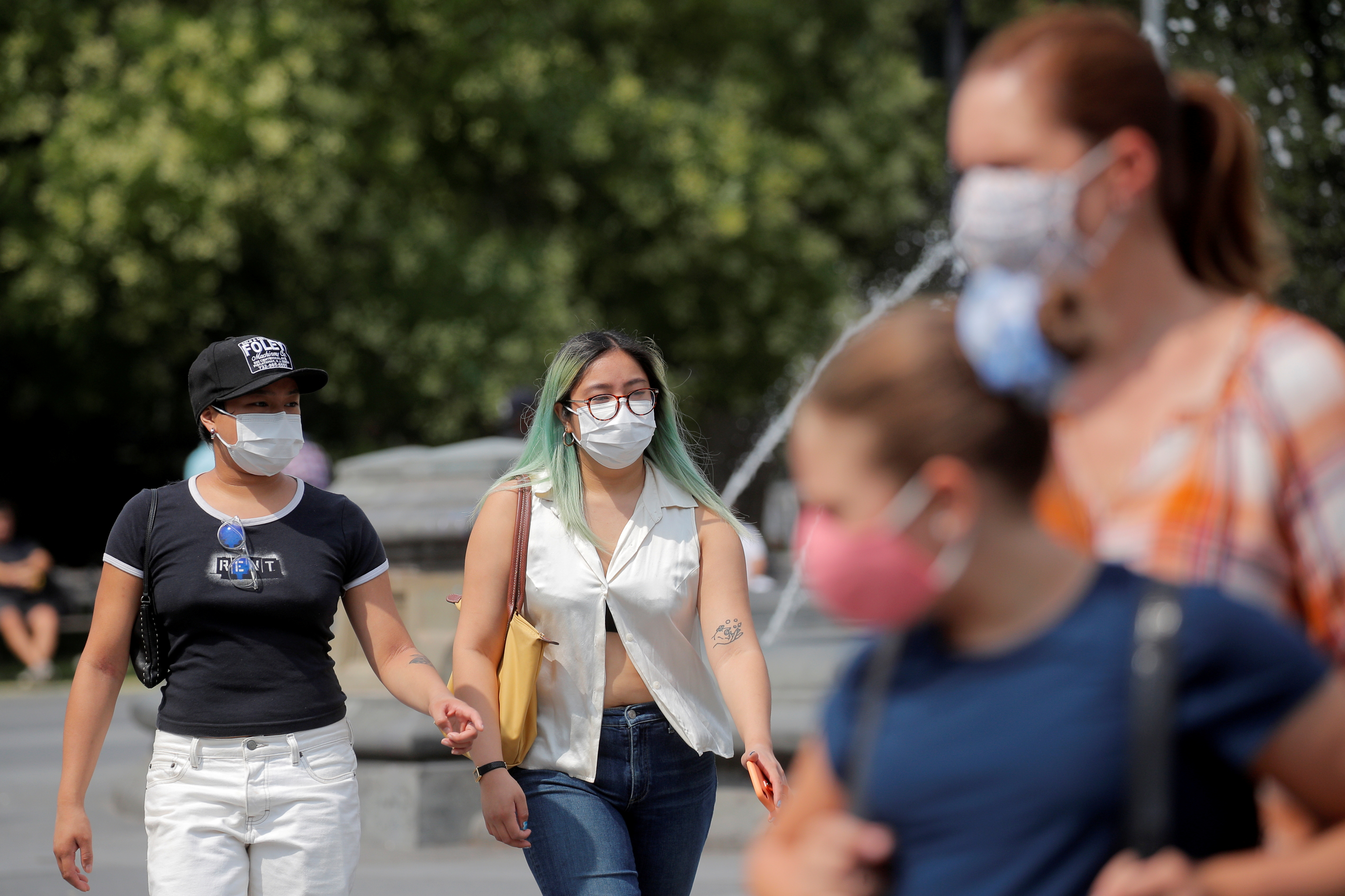 People wear masks, as cases of the infectious Delta variant of coronavirus disease (COVID-19) continue to rise, in Washington Square Park in New York City, U.S., July 22, 2021.  REUTERS/Brendan McDermid/File Photo