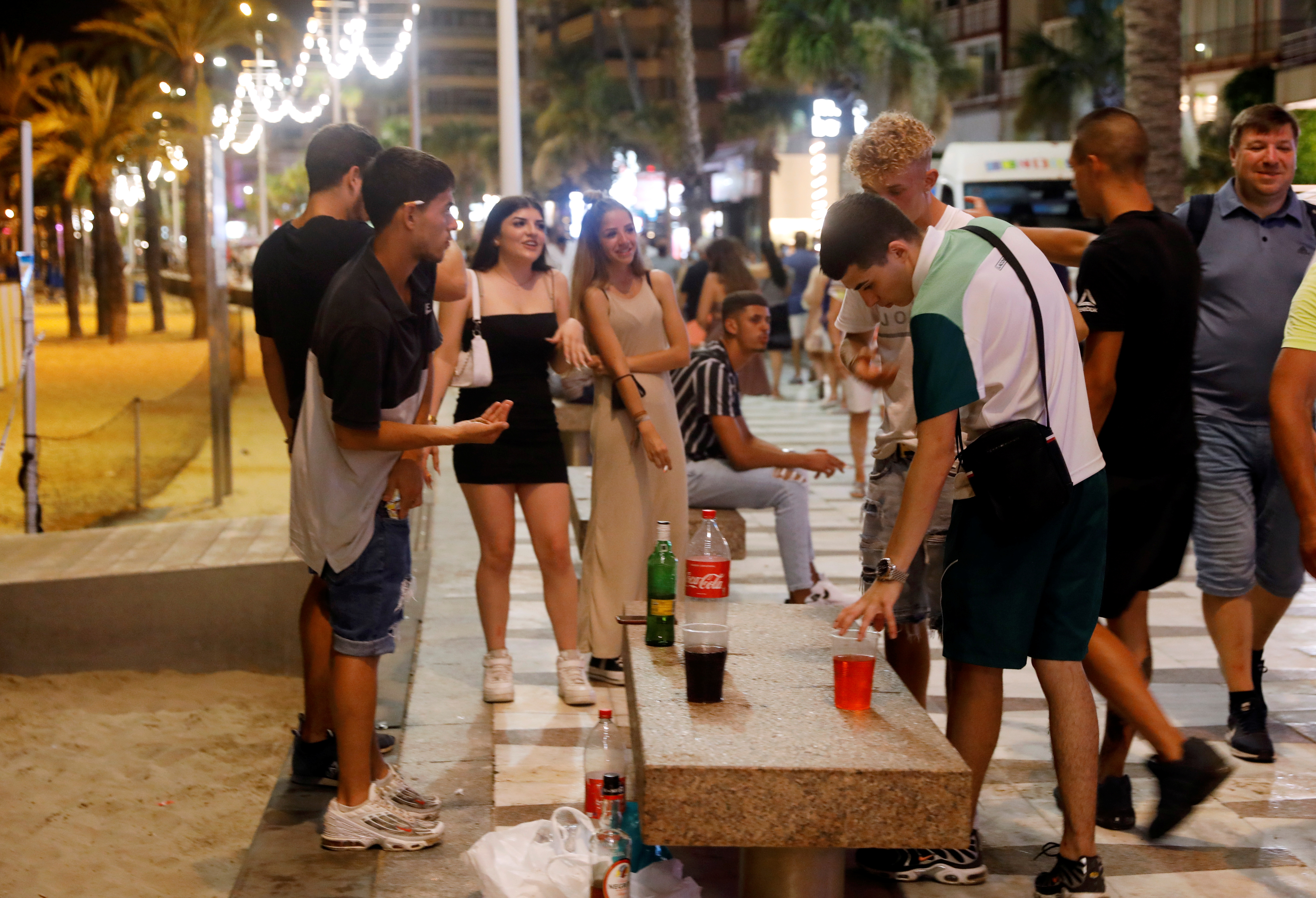 Youngsters party on Levante beach before closing for a night-time curfew which comes into effect tonight (01:00-06:00), as regional authorities in Valencia try to contain the rise of the coronavirus disease (COVID-19), in Benidorm, Spain July 25, 2021. REUTERS/Eva Manez