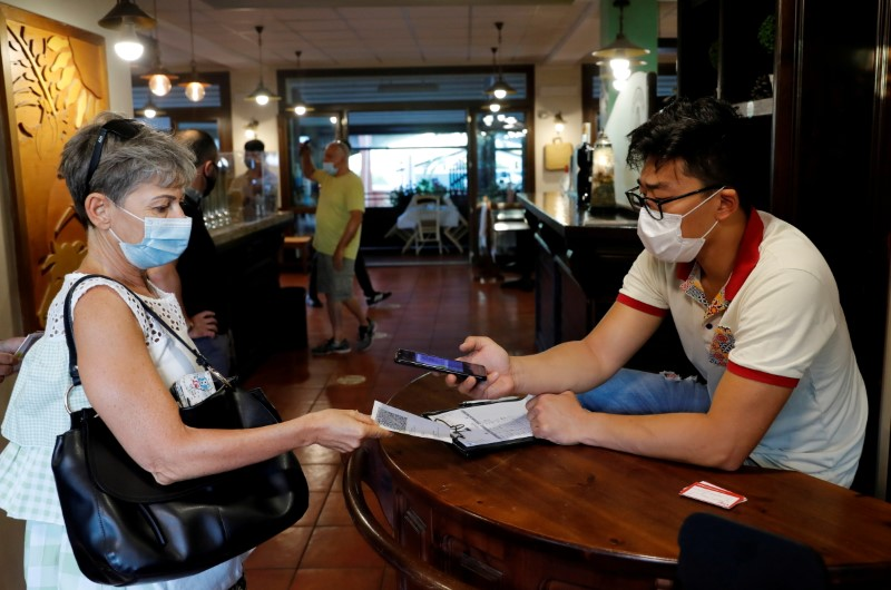 A woman has her Green Pass (health pass) checked before entering a pizzeria as Italy brings in tougher restrictions where a proof of immunity will be required to access an array of services and leisure activities, in Rome, Italy, August 6, 2021. REUTERS/Remo Casilli/File Photo
