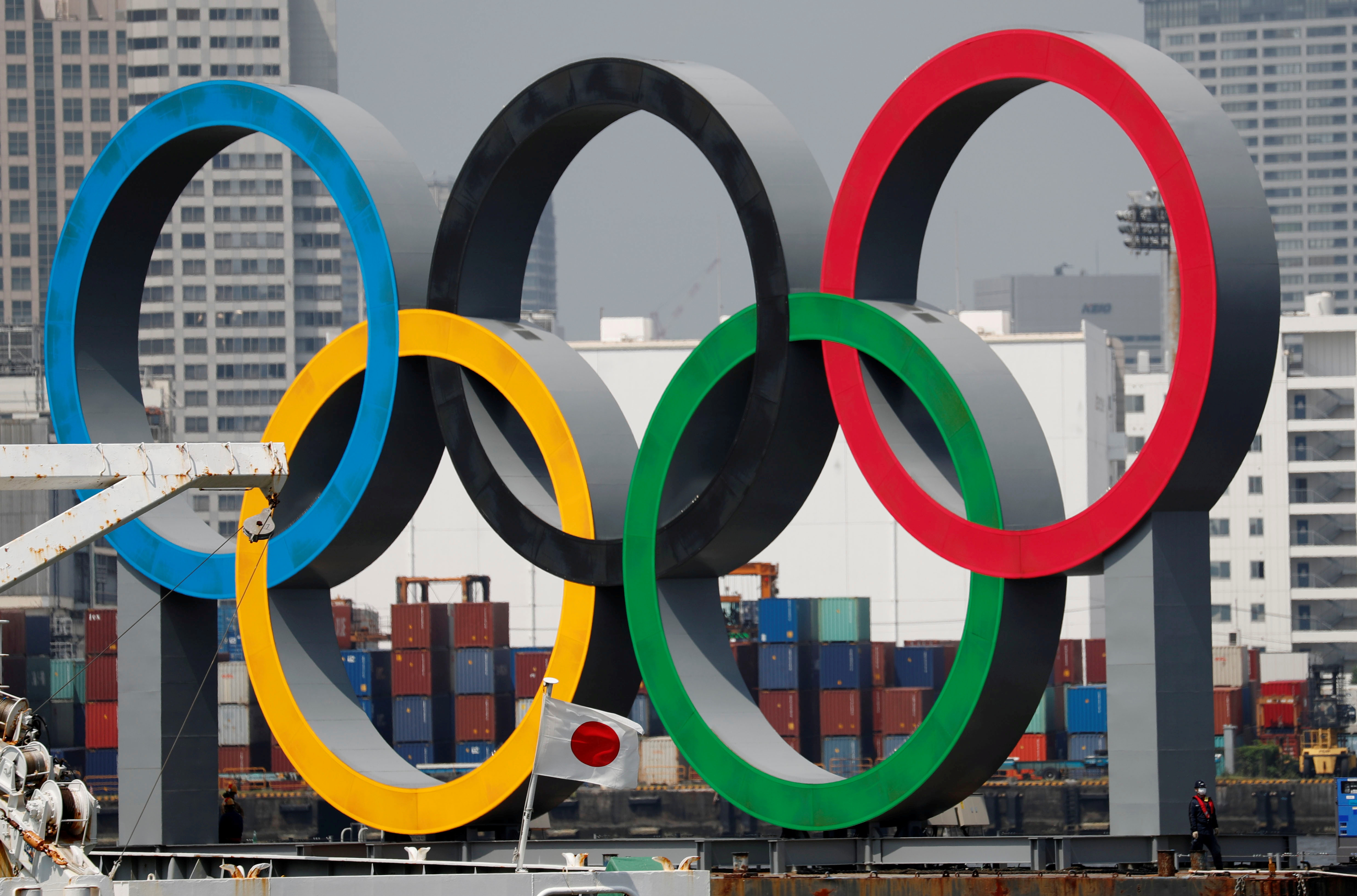 The giant Olympic rings, which are being temporarily removed for maintenance, are seen behind Japan's national flag, amid the coronavirus disease (COVID-19) outbreak, at the waterfront area at Odaiba Marine Park in Tokyo, Japan August 6, 2020. REUTERS/Kim Kyung-Hoon/File Photo