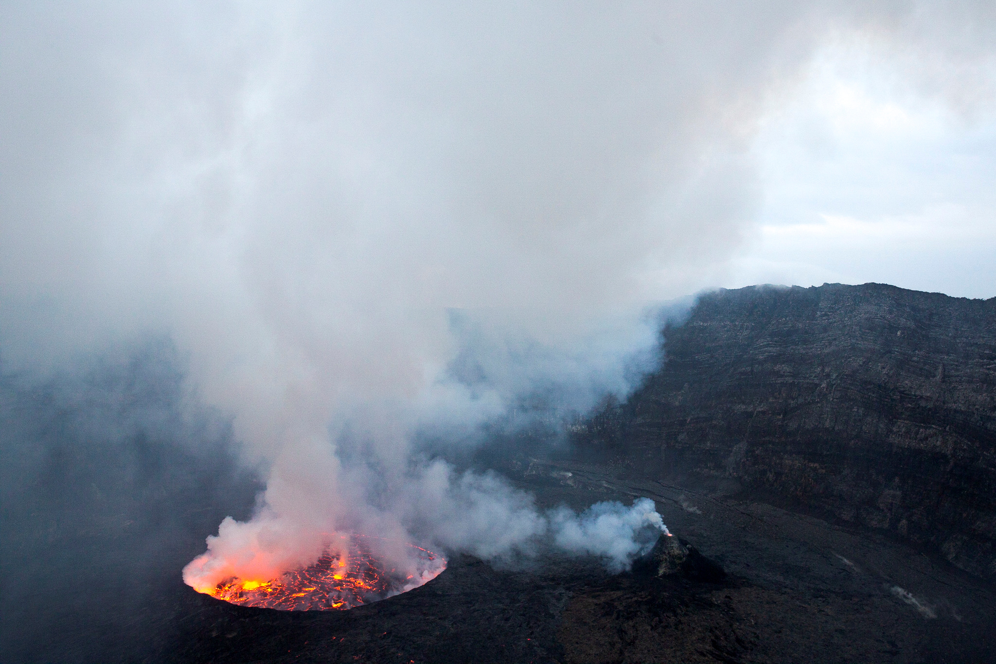 A lava lake and a mini cone inside the Mount Nyiragongo volcano crater spew gas into the sky inside the Virunga National Park, near Goma, in the eastern Democratic Republic of Congo February 12, 2021. Picture taken February 12, 2021. REUTERS/Hereward Holland