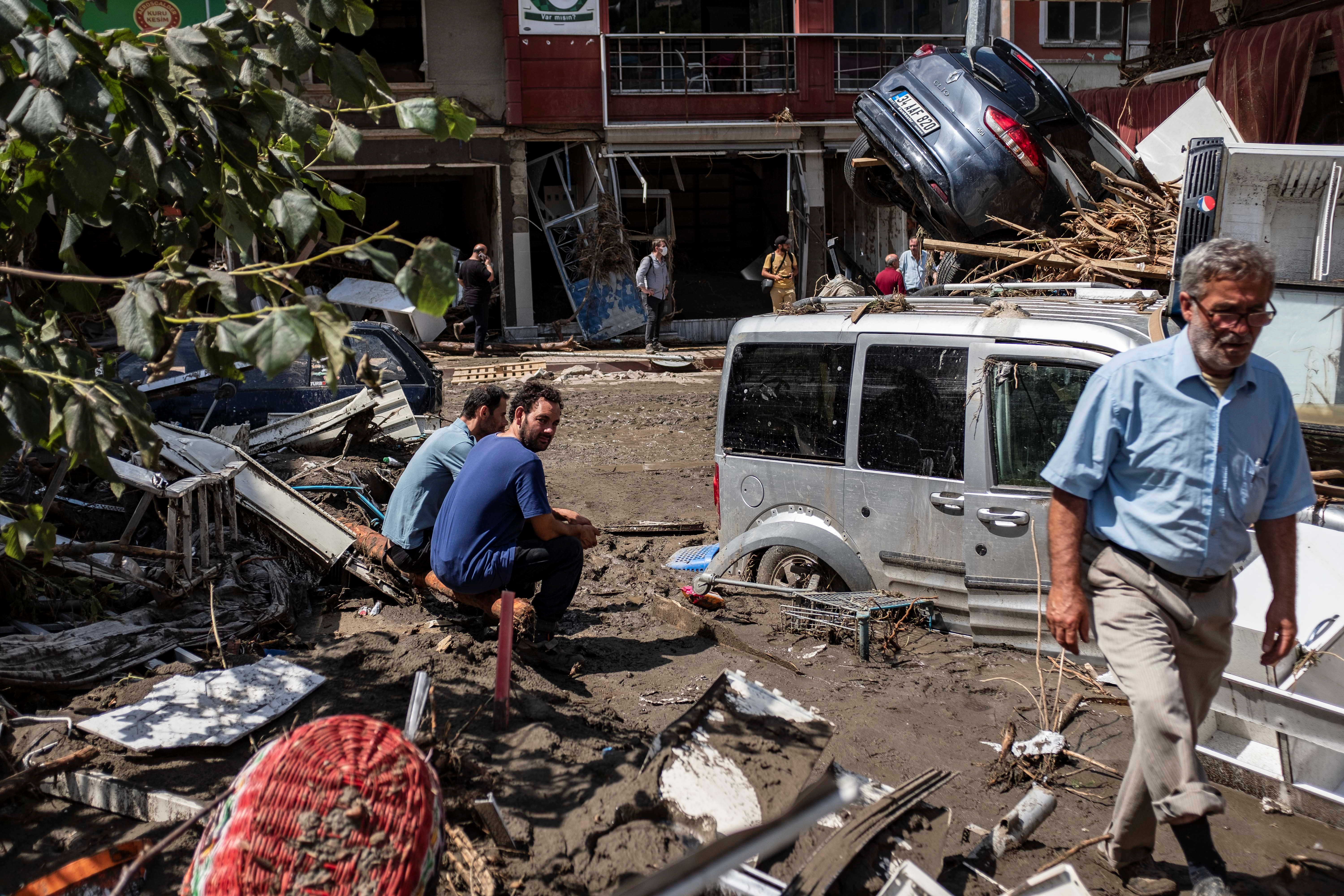 Locals watch as vehicles are seen in the debris of flash floods that swept through towns in the Turkish Black Sea region in Bozkurt, a town in Kastamonu province, Turkey, August 13, 2021. Can Erok/Demiroren Visual Media via REUTERS ATTENTION EDITORS - THIS PICTURE WAS PROVIDED BY A THIRD PARTY. NO RESALES. NO ARCHIVE. TURKEY OUT. NO COMMERCIAL OR EDITORIAL SALES IN TURKEY.