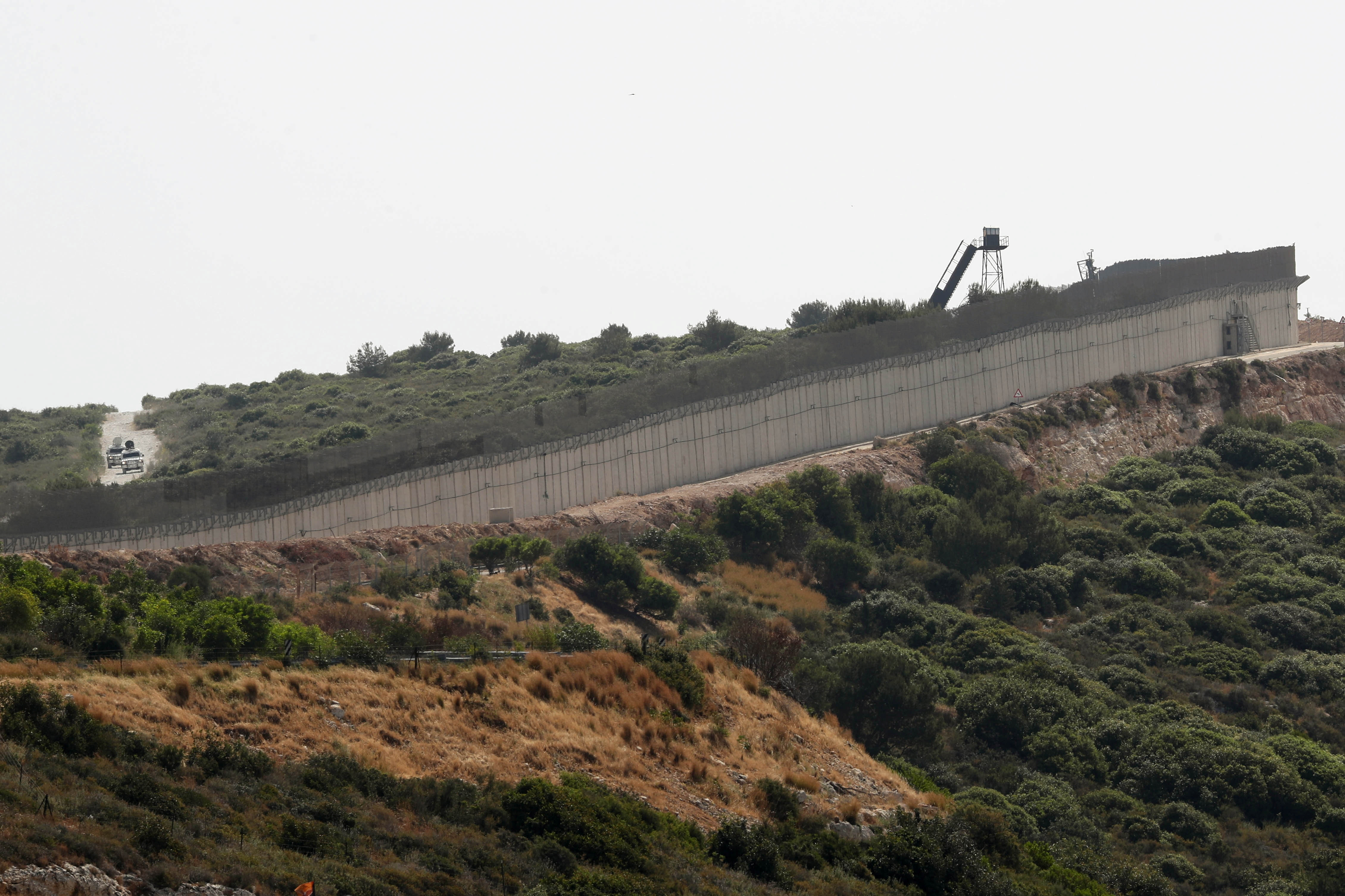 Vehicles are seen behind the border wall between Israel and Lebanon, as seen from Rosh Hanikra, northern Israel May 4, 2021. REUTERS/Ammar Awad