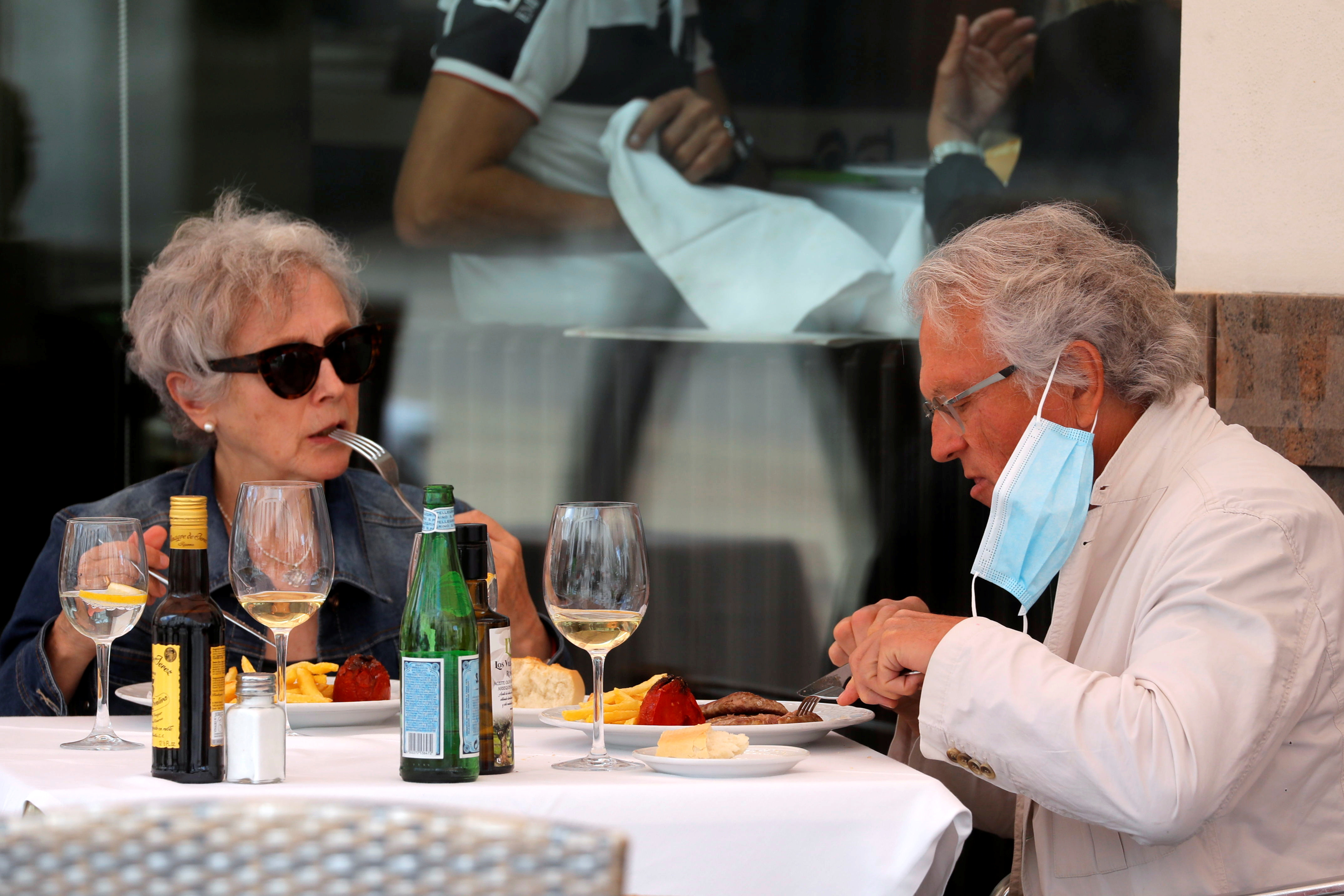 People eat on a restaurant terrace, amid the coronavirus disease (COVID-19) pandemic, in Ronda, Spain, June 18, 2021. Spanish Prime Minister Pedro Sanchez announced on Friday, the lifting of the blanket obligation to wear masks outdoors from June 26. REUTERS/Jon Nazca