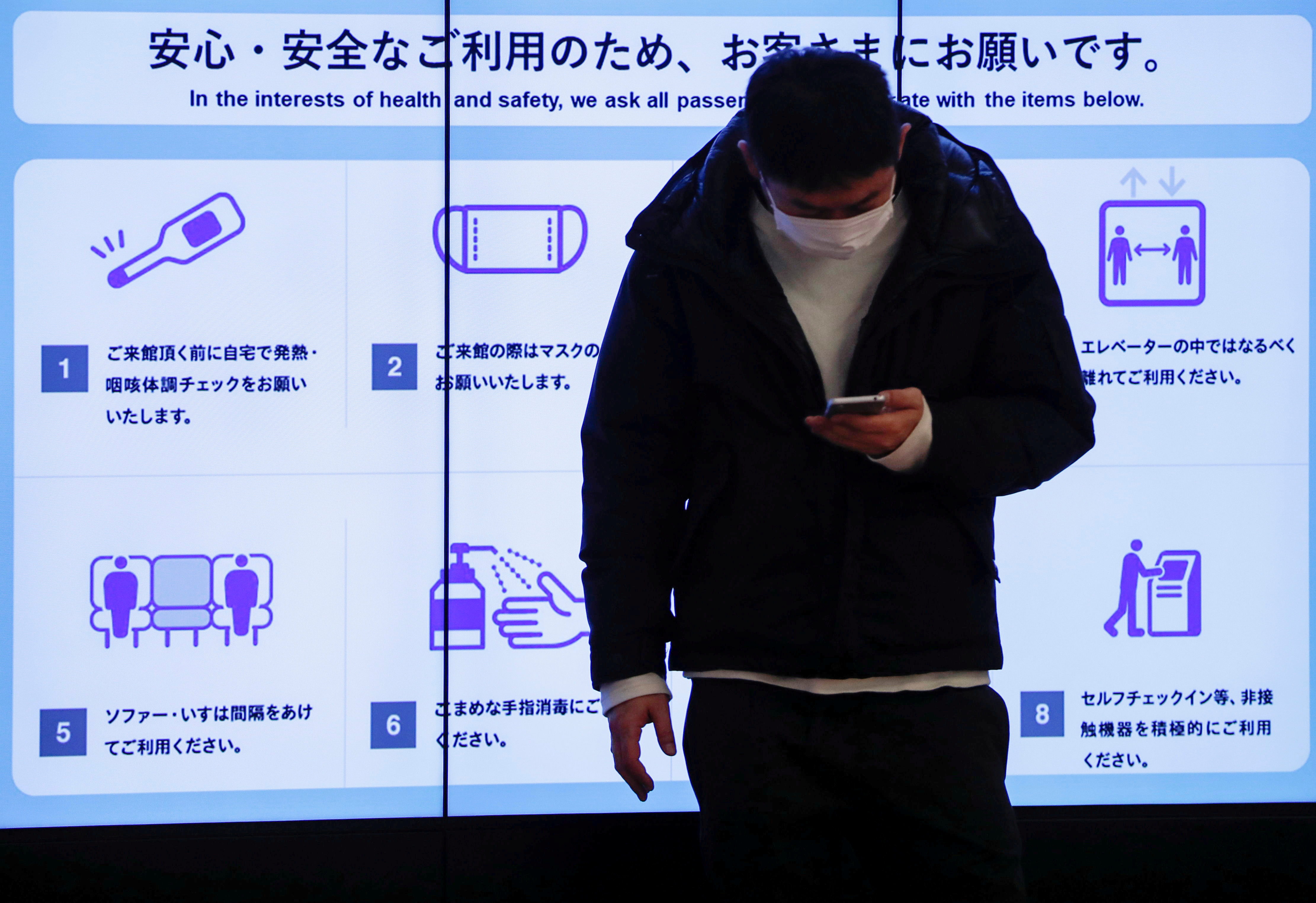 A man wearing a protective face mask stands in front of an electric screen displaying initiatives to prevent infections at the arrival zone of the international flight terminal at Tokyo International Airport, commonly know as Haneda airport, amid the coronavirus disease (COVID-19) outbreak, in Tokyo, Japan December 28, 2020.  REUTERS/Issei Kato/File Photo