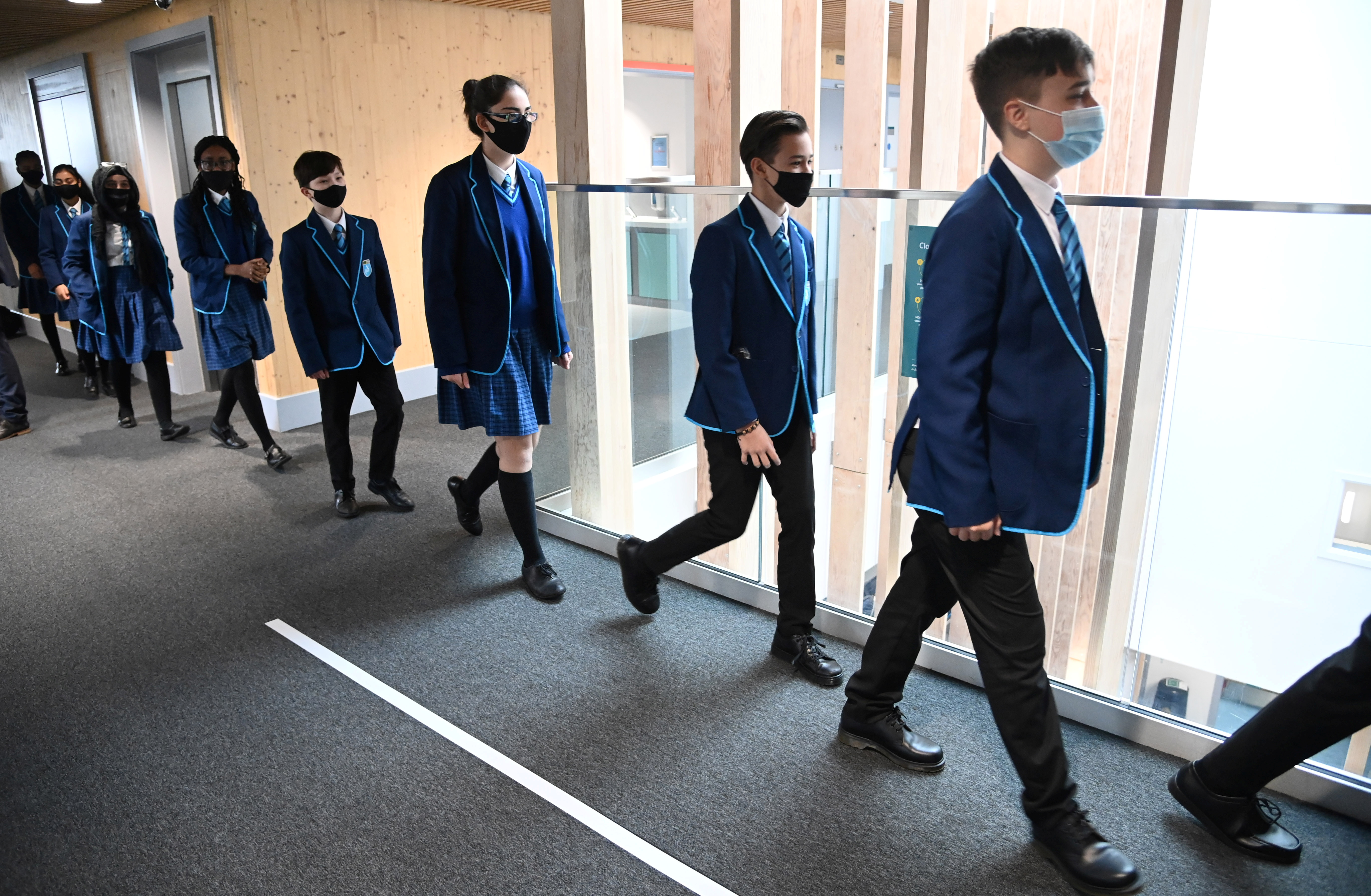 Year 9 students wear protective face masks as they walk between classrooms on the first day back at school, as the coronavirus disease (COVID-19) lockdown begins to ease at Harris Academy Sutton, south London, Britain, March 8, 2021. REUTERS/Toby Melville