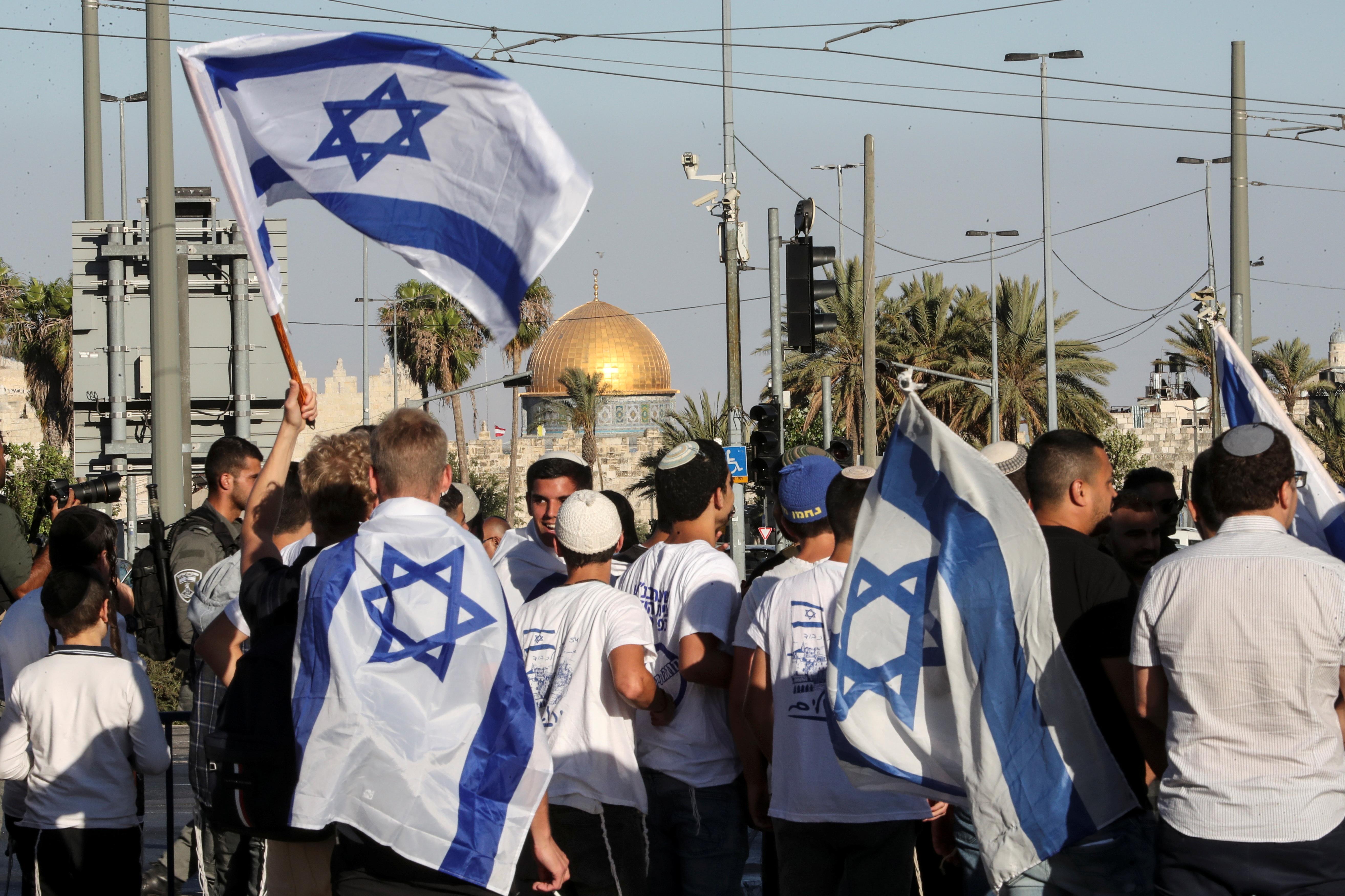 Israelis walk with flags outside Jerusalem's Old City,  June 15,2021. REUTERS/Ronen Zvulun