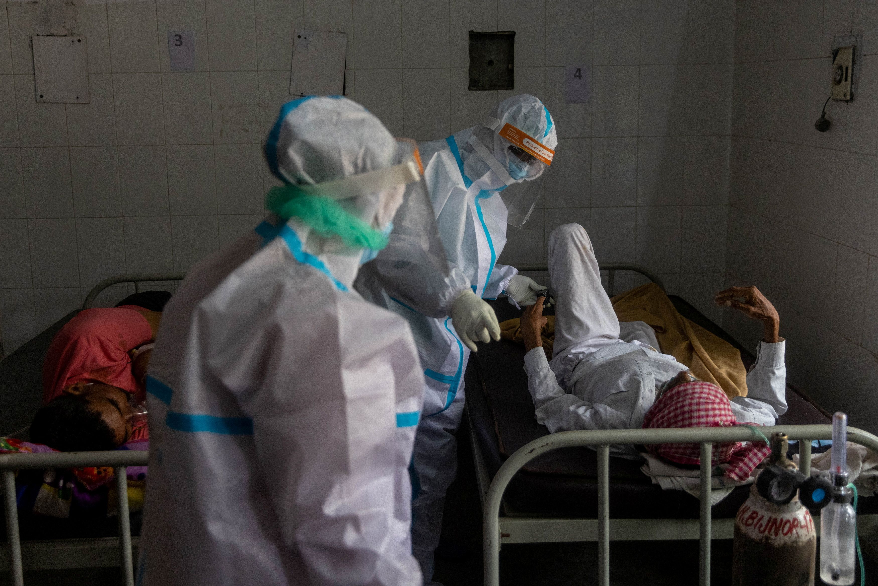 Medics tend to a man with breathing problems inside a COVID-19 ward of a government-run hospital, amidst the coronavirus disease (COVID-19) pandemic, in Bijnor district, Uttar Pradesh, India, May 11, 2021. REUTERS/Danish Siddiqui