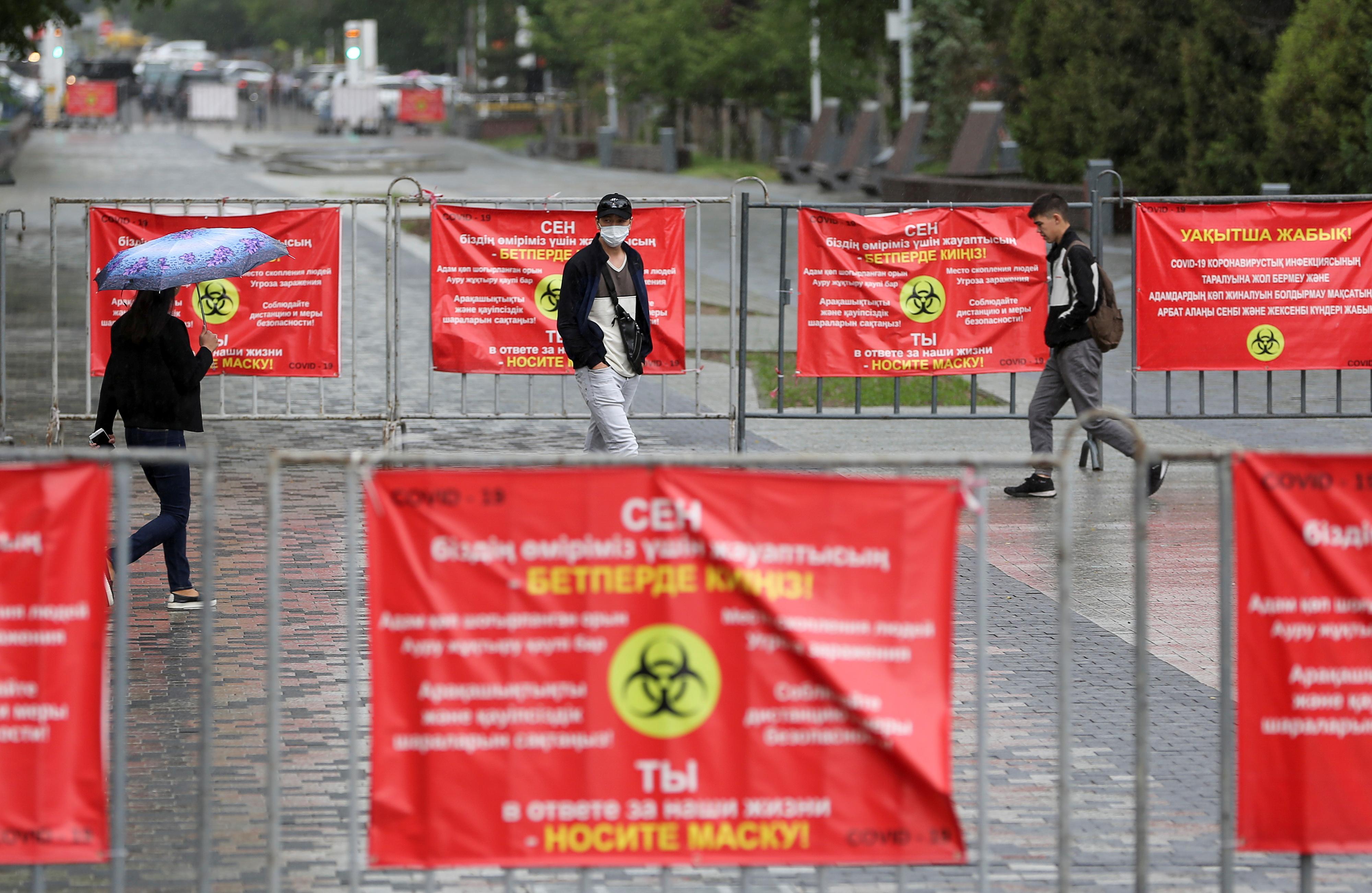 People walk past banners informing of preventive measures against the coronavirus disease (COVID-19) in Almaty, Kazakhstan May 20, 2021. REUTERS/Pavel Mikheyev
