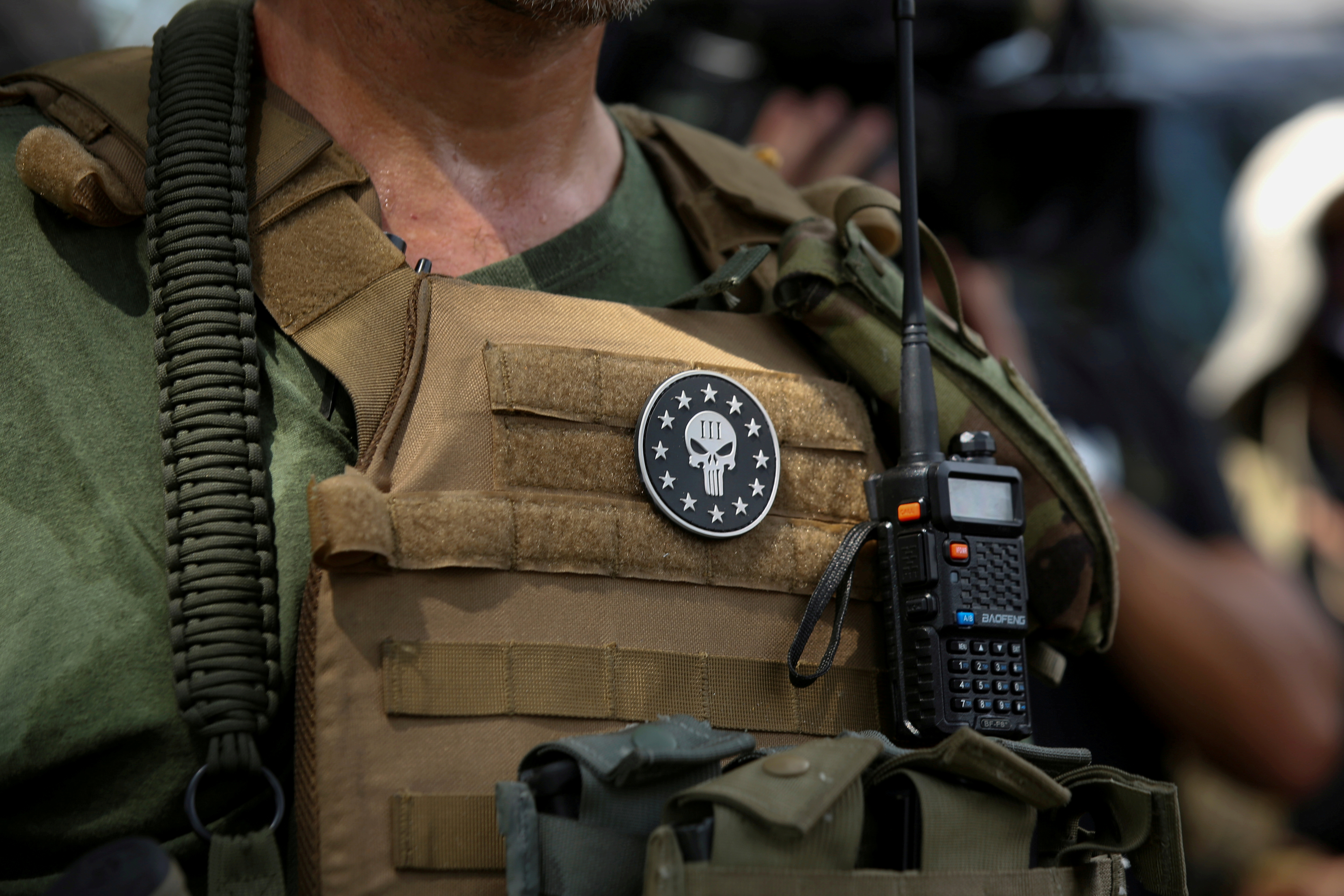 A militia member with body armor and a Three Percenters militia patch stands in Stone Mountain as various militia groups stage rallies at Stone Mountain, Georgia, U.S. August 15, 2020.  REUTERS/Dustin Chambers/File Photo