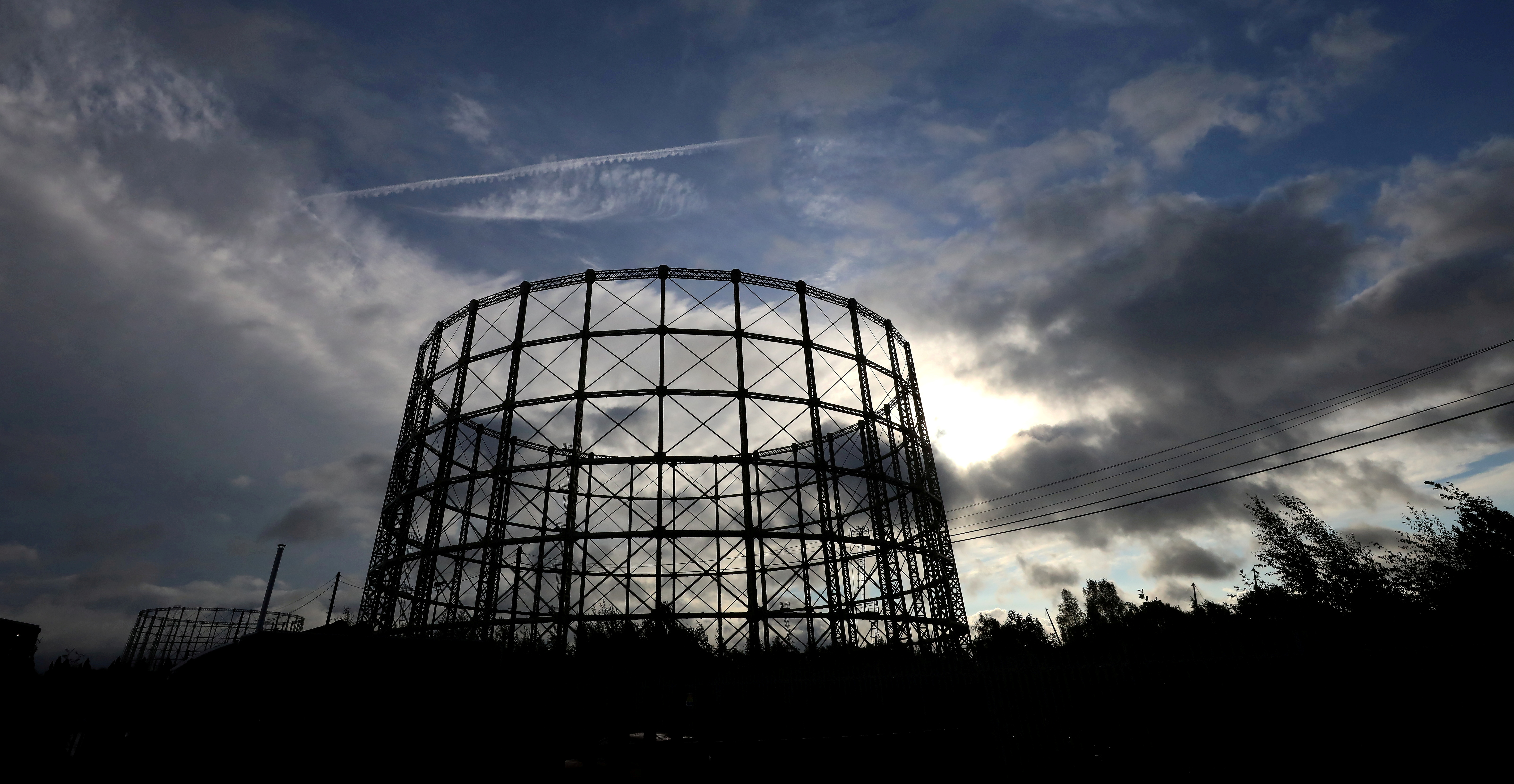 The sun appears through the clouds behind a disused gas holder in Manchester, Britain, September 23, 2021. REUTERS/Phil Noble/File Photo