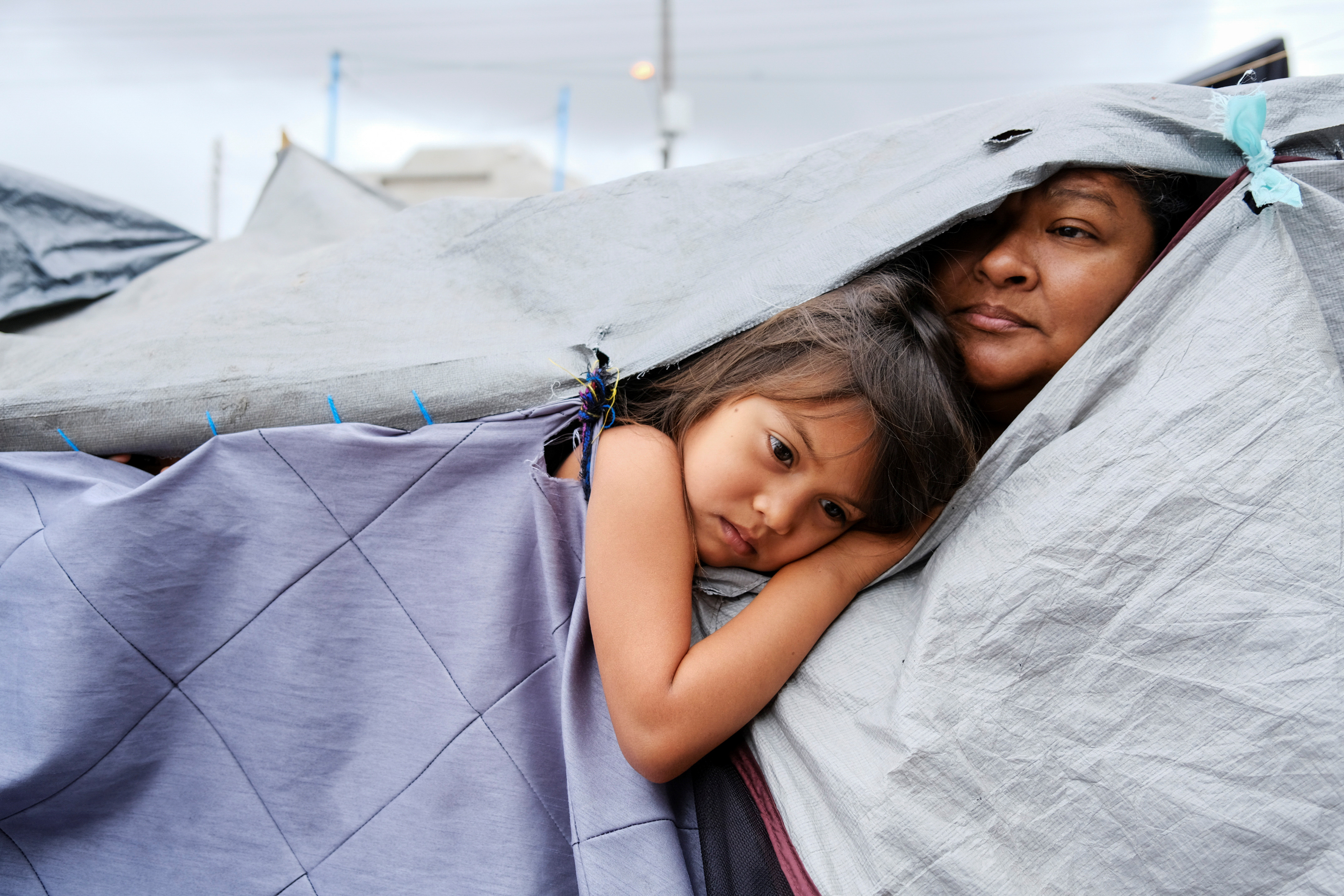 Honduran migrants Kami, 5, and her aunt Mariana listen as other migrants discuss hygiene norms within the migrant camp, at a makeshift camp at the El Chaparral border port of entry with the U.S., in Tijuana, Mexico April 22, 2021. Picture taken April 22, 2021. REUTERS/Toya Sarno Jordan