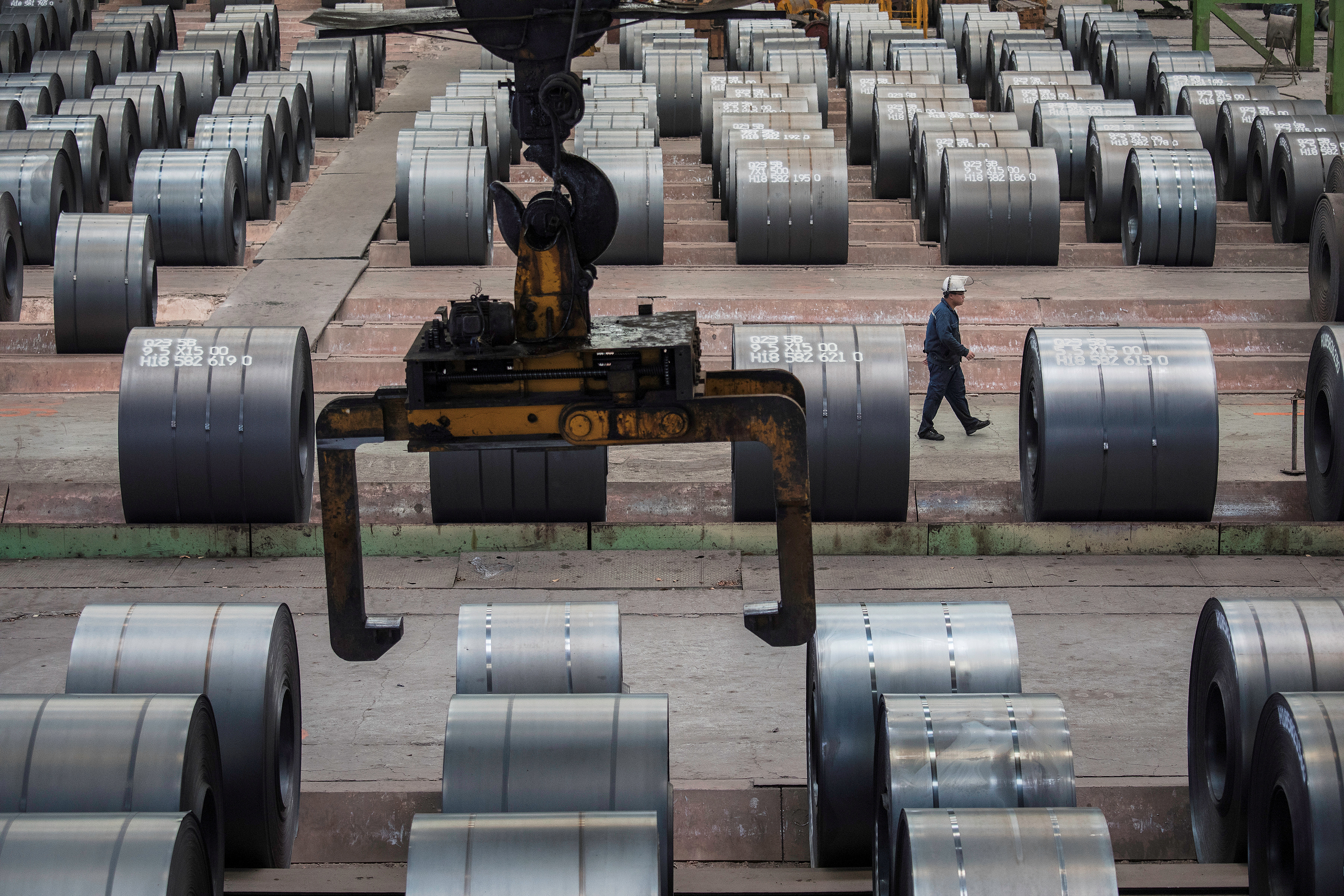 A worker walks past steel rolls at the Chongqing Iron and Steel plant in Changshou, Chongqing, China August 6, 2018. REUTERS/Damir Sagolj