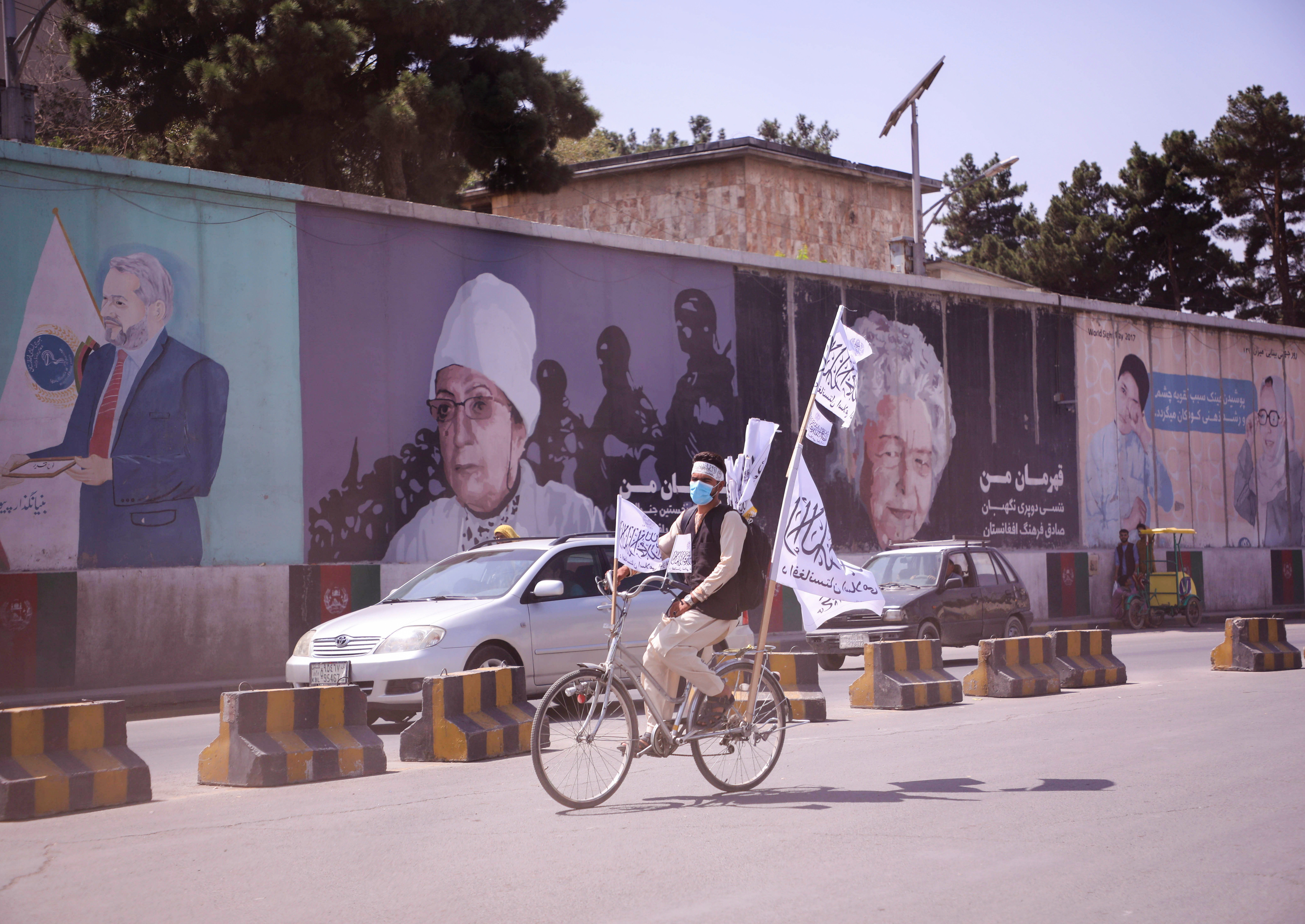 An Afghan man rides on his bicycle as he holds the Taliban flag in Kabul, Afghanistan, September 2, 2021. REUTERS/Stringer