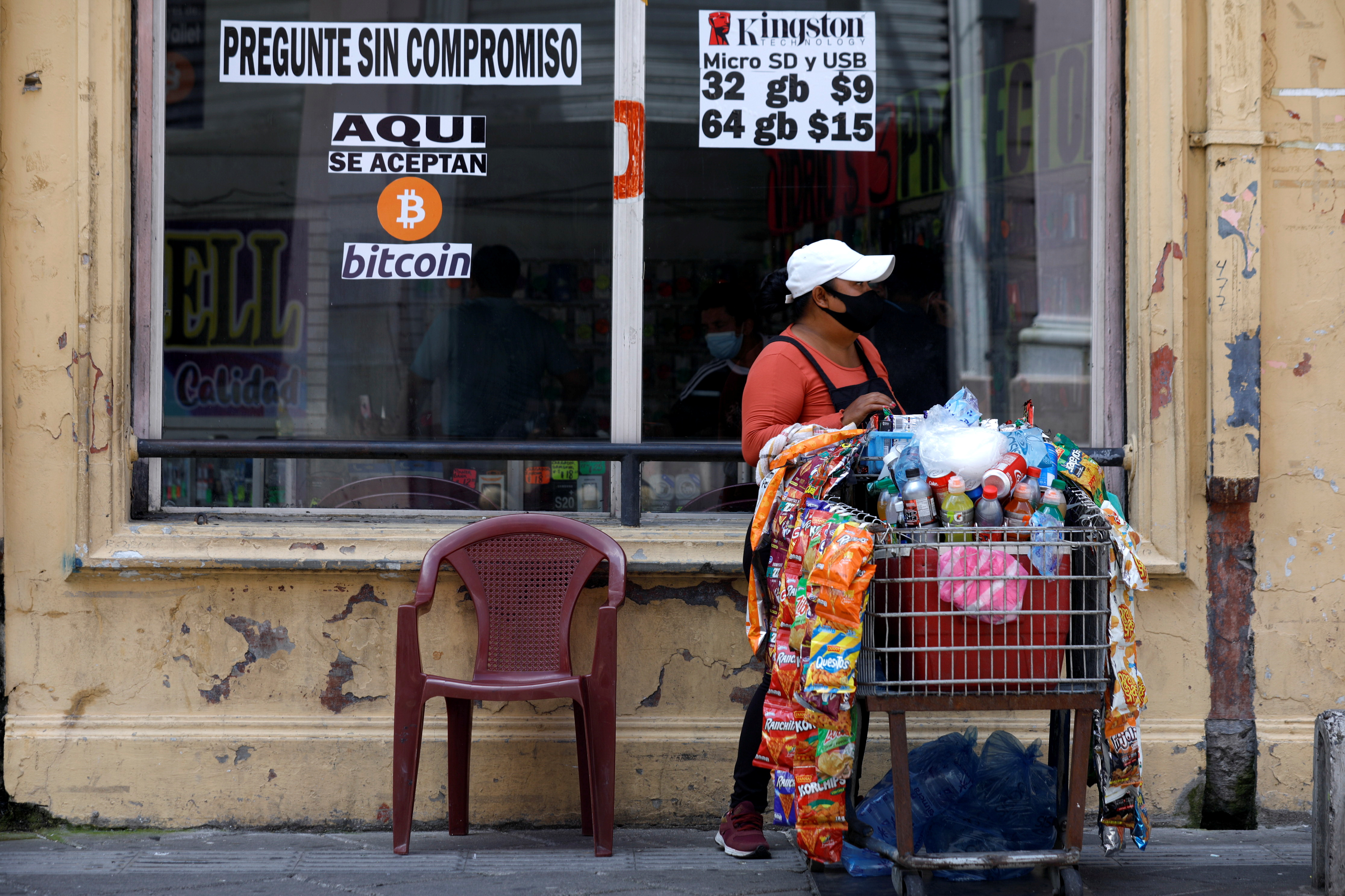 A woman vends by a sign that reads,