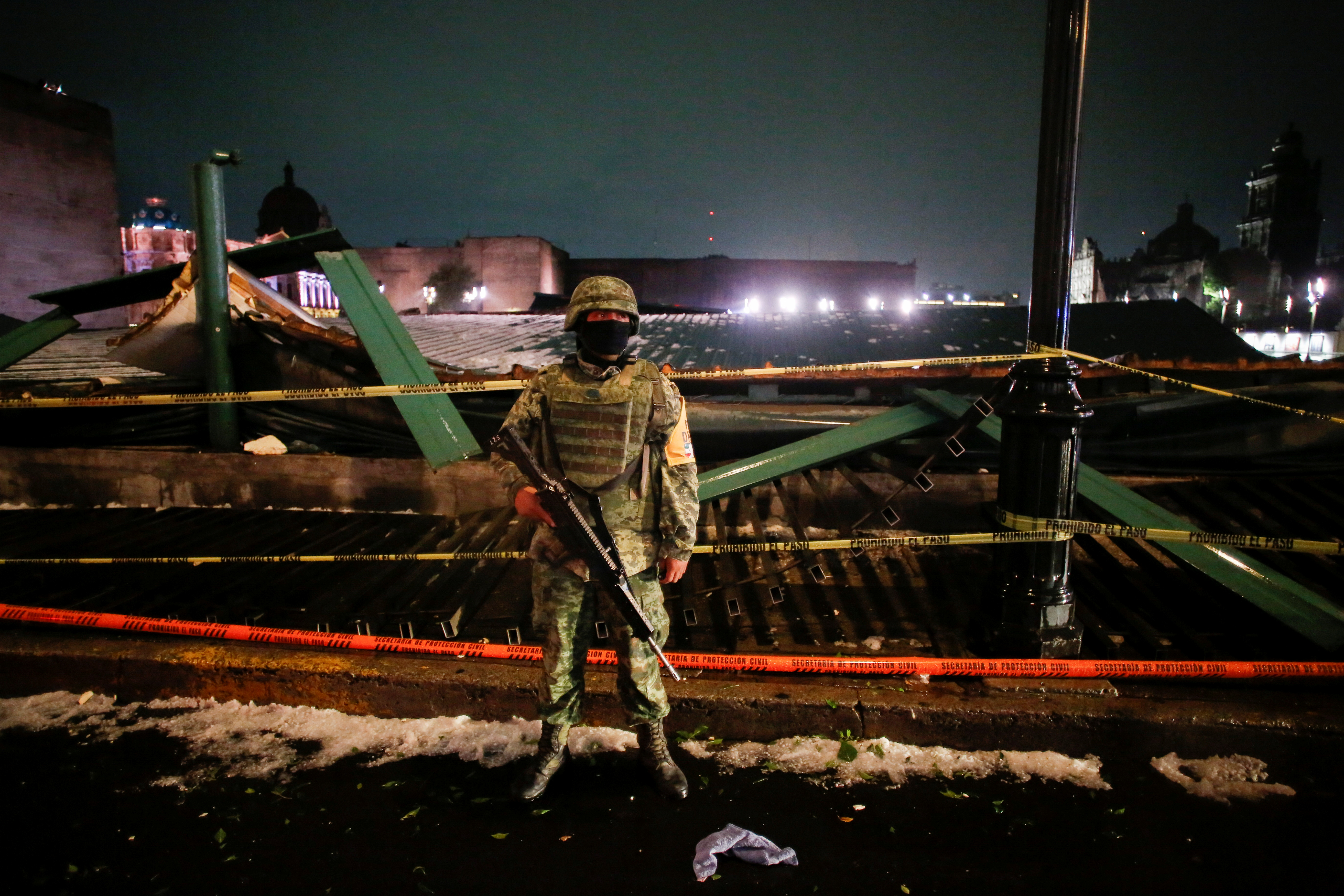 A soldier keeps watch at a scene where the roof protecting the