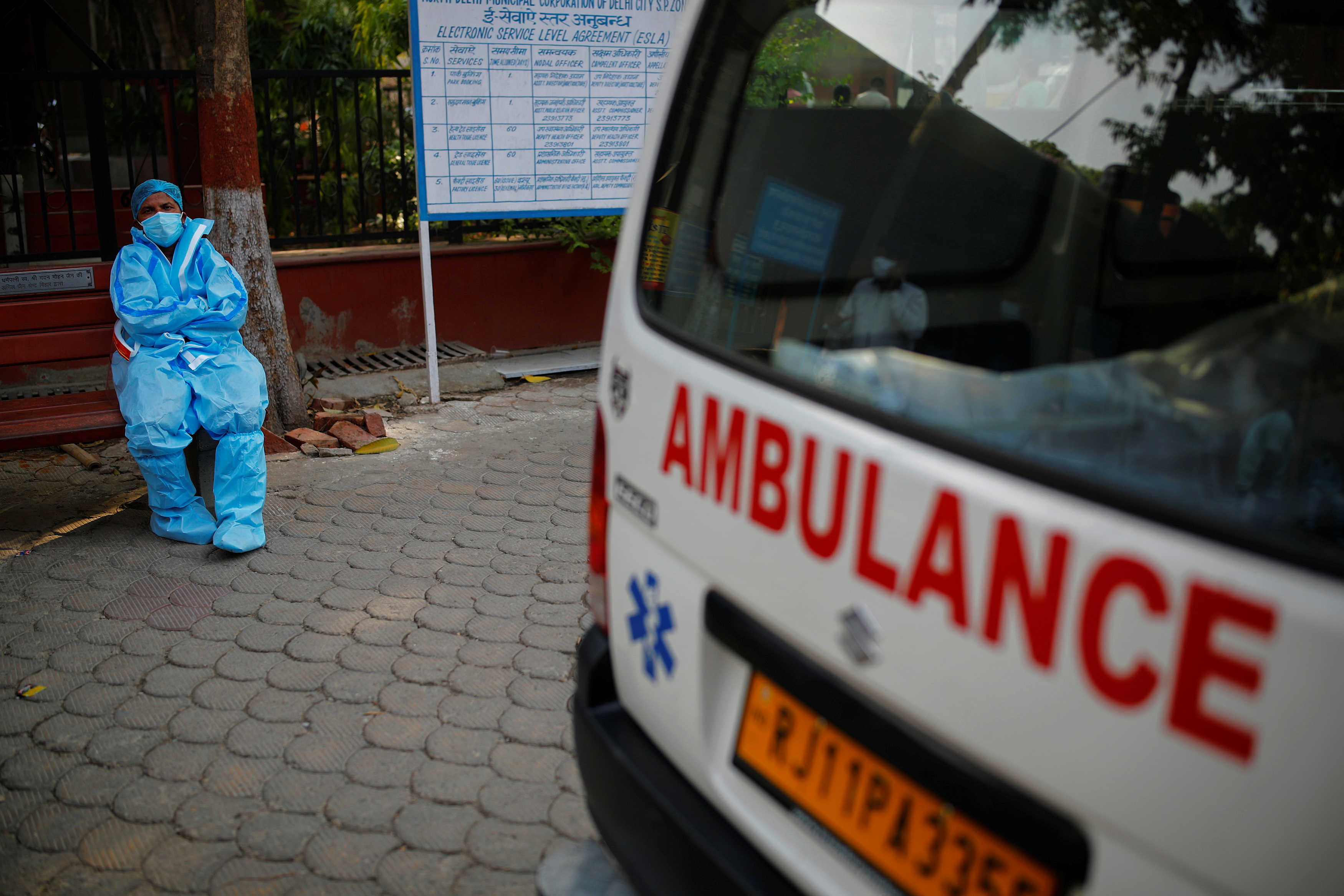 A health worker rests as he sits next to his ambulance carrying a dead body of a victim who died due to the coronavirus disease (COVID-19), at a crematorium in New Delhi, India, May 10, 2021. REUTERS/Adnan Abidi/File Photo