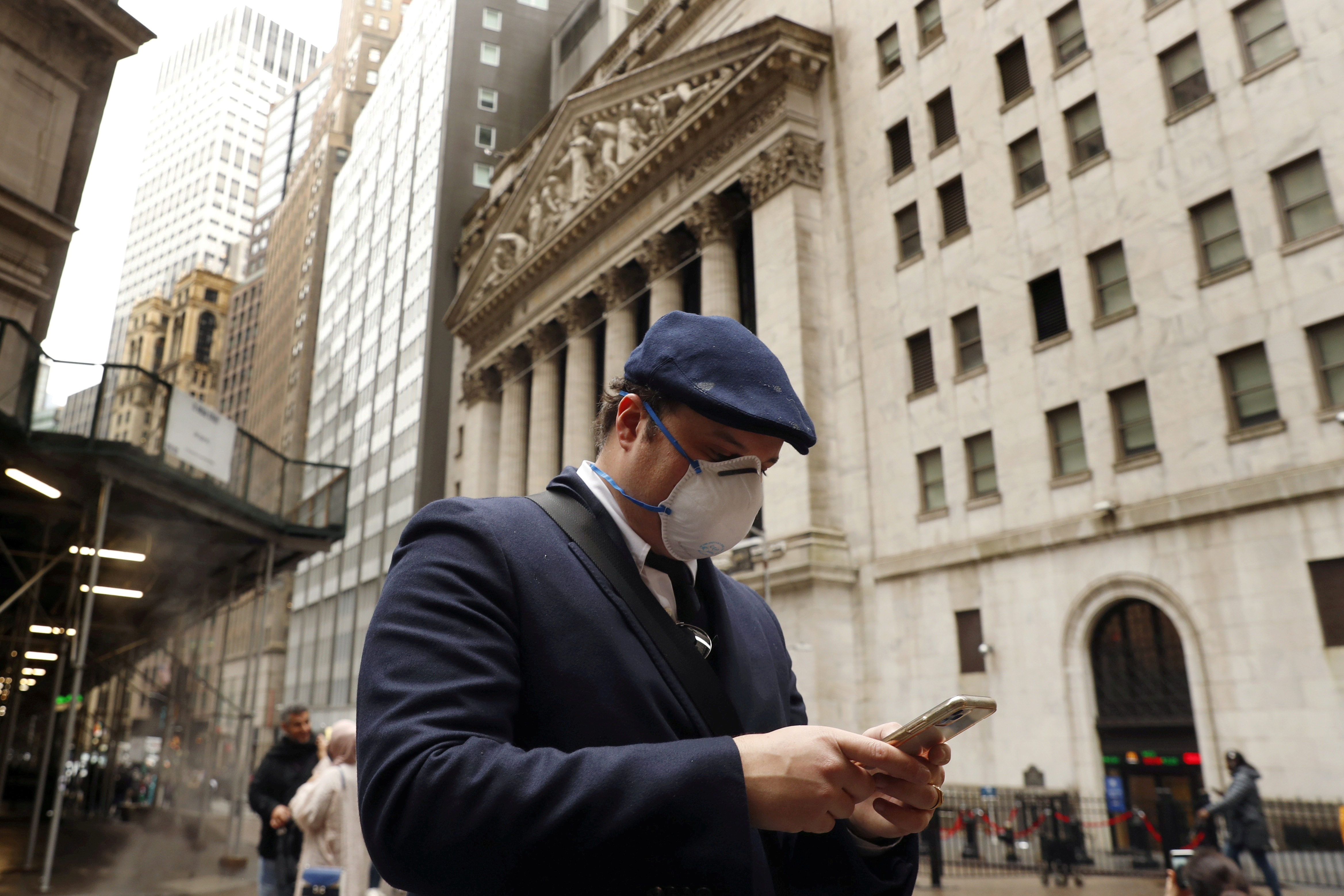 A man walks past the New York Stock Exchange on the corner of Wall and Broad streets in New York City, New York, U.S., March 13, 2020. REUTERS/Lucas Jackson