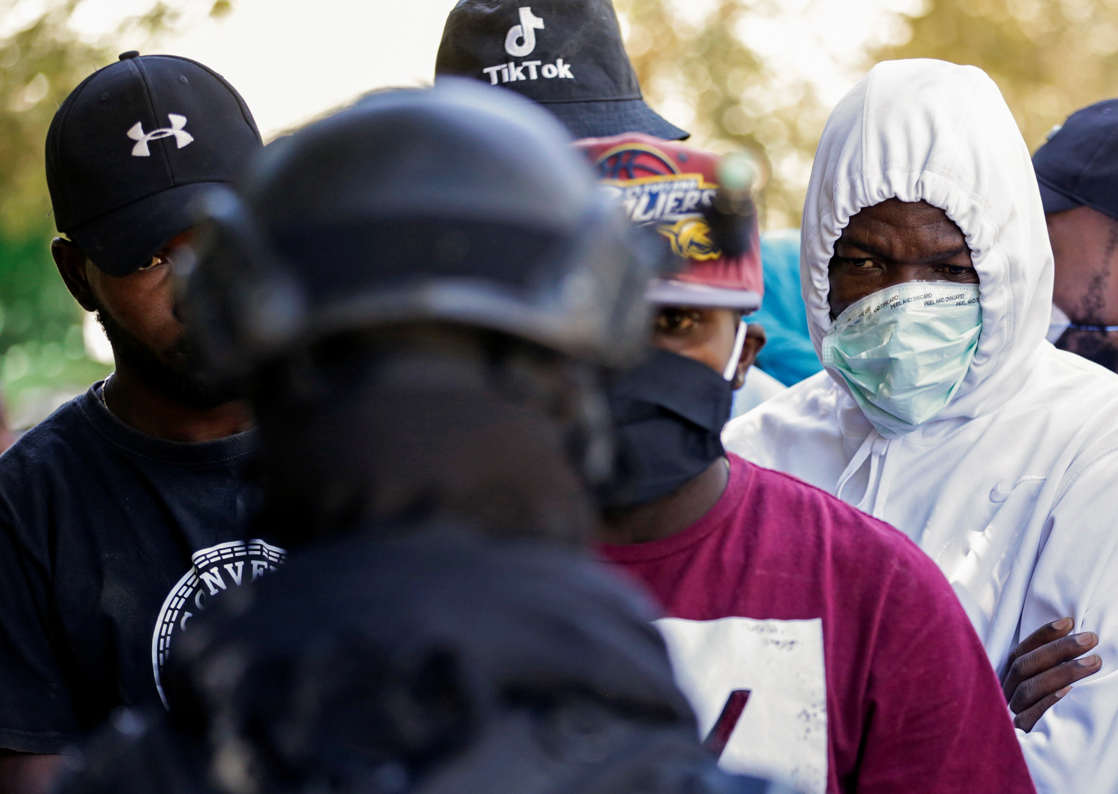 Migrants speak with a Mexican police officer in a makeshift camp at Braulio Fernandez Ecological Park near the border with the U.S., in Ciudad Acuna, Mexico, September 24, 2021. REUTERS/Daniel Becerril