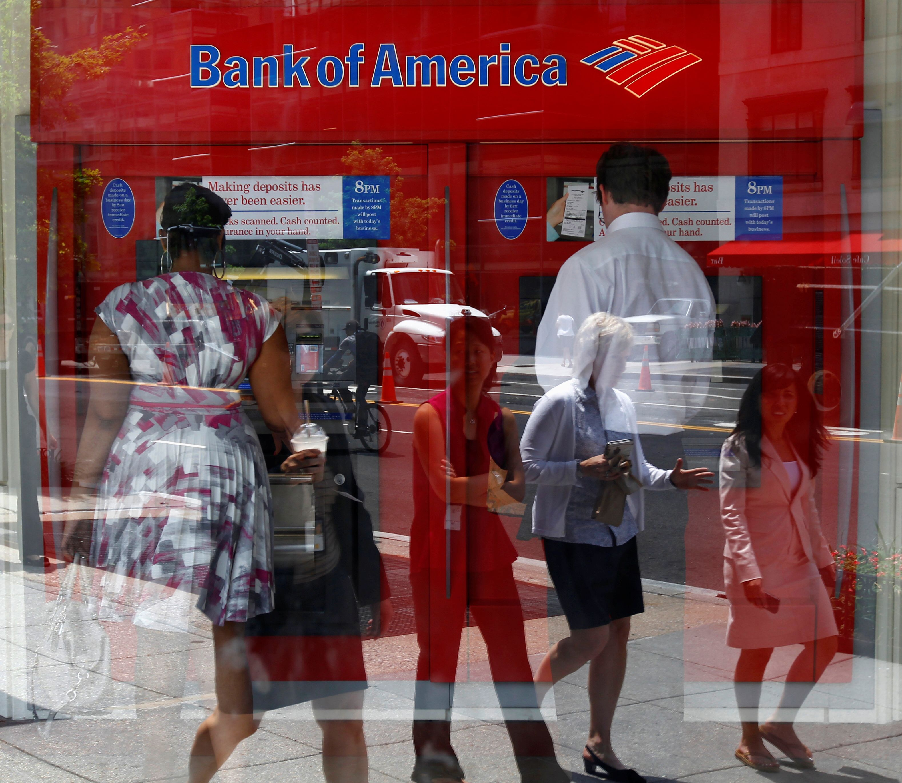 Pedestrians are reflected in the window as customers conduct transactions at a Bank of America ATM in Washington July 19, 2011.   REUTERS/Kevin Lamarque/File Photo