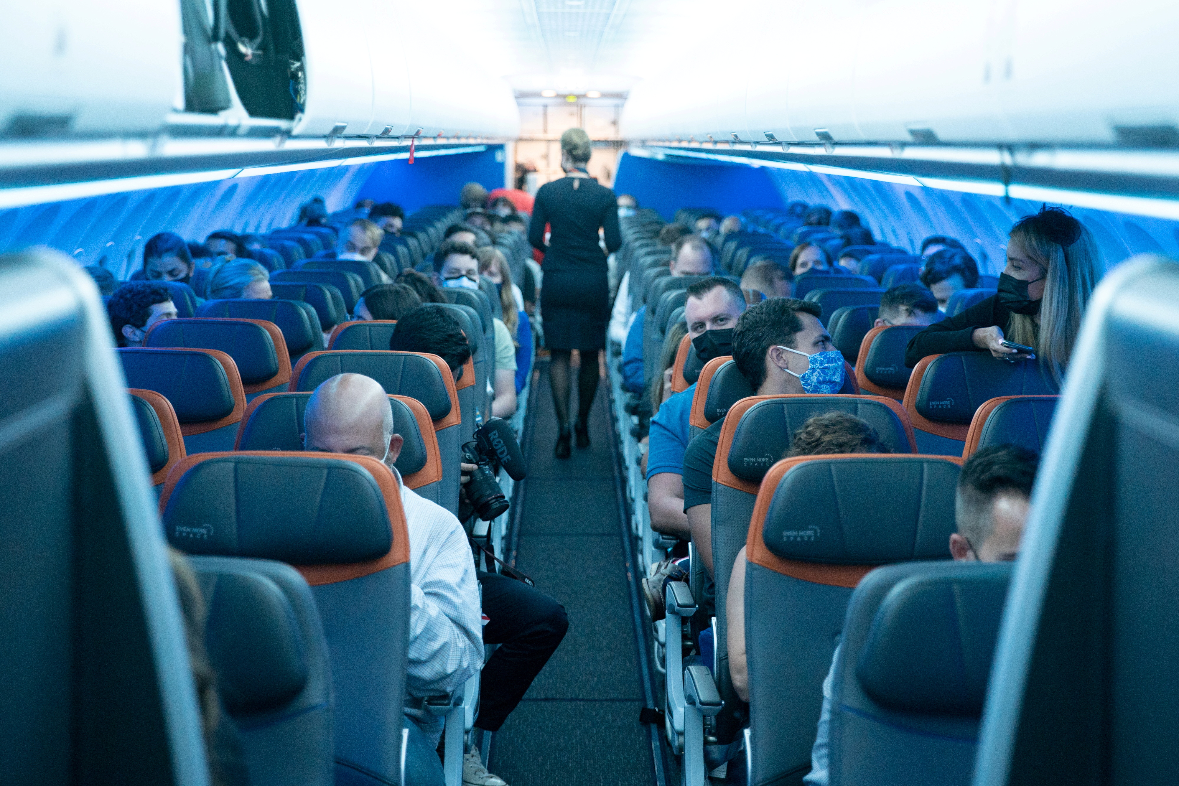 Passengers wearing protective masks are seen aboard before a JetBlue flight to London at JFK International Airport in the Queens borough of New York City, New York, U.S., August 11, 2021. REUTERS/Jeenah Moon