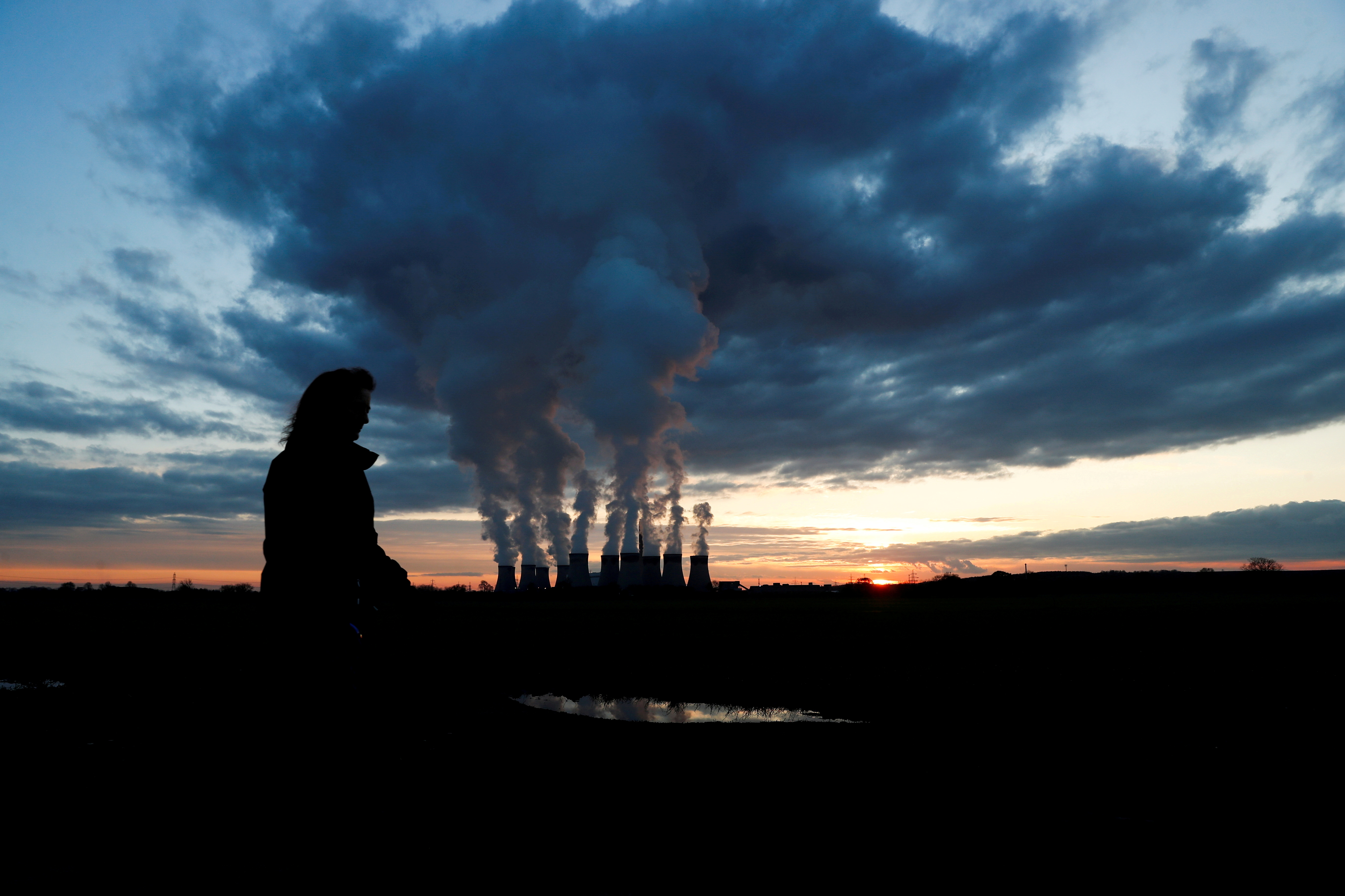 A woman walks a dog past Drax power station during the sunset in Drax, North Yorkshire, Britain, November 27, 2020. REUTERS/Lee Smith