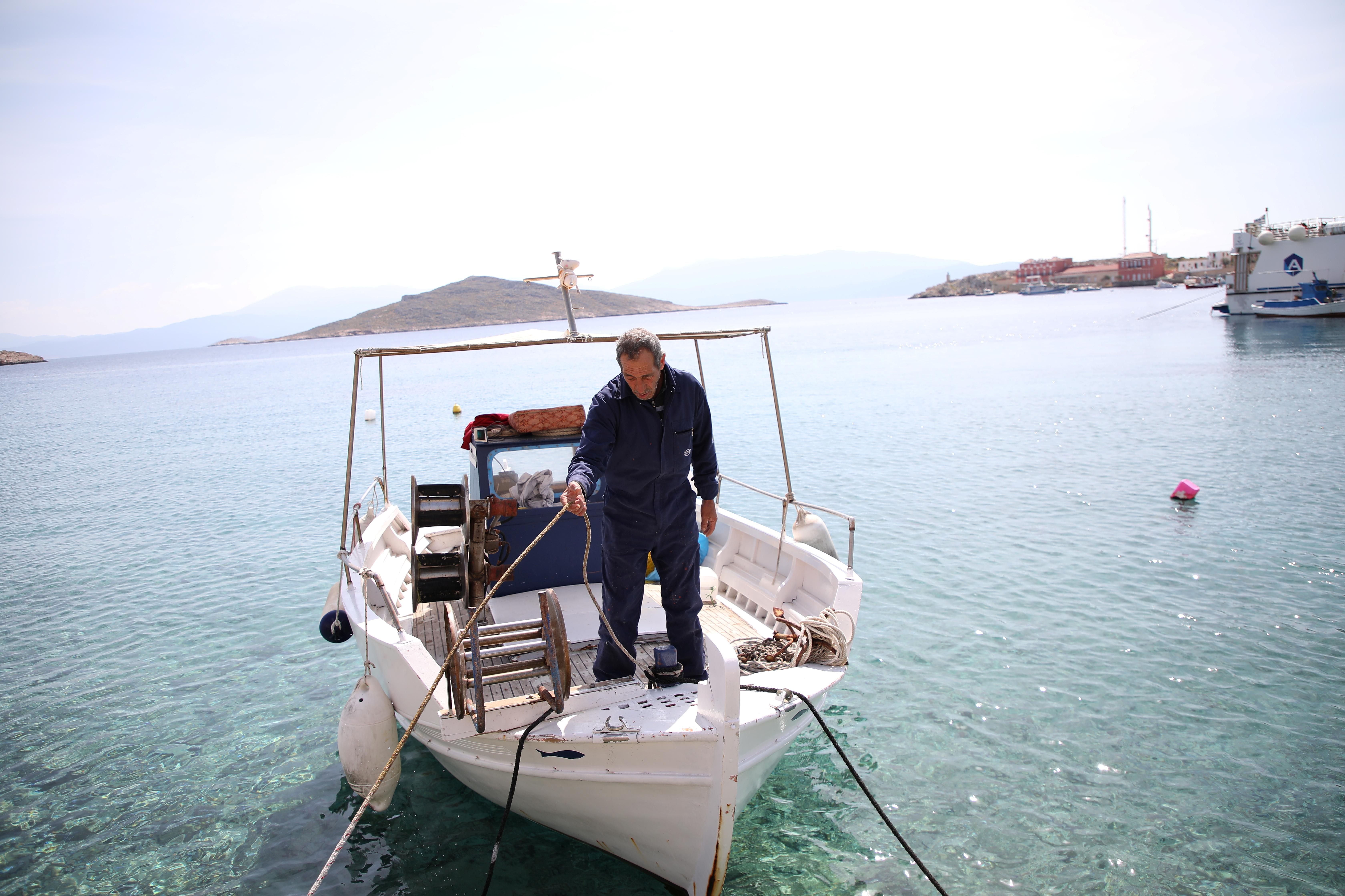 A fisherman prepares to moor his boat at the port, amid the coronavirus disease (COVID-19) pandemic, on the island of Halki, Greece, April 13, 2021. REUTERS/Louiza Vradi